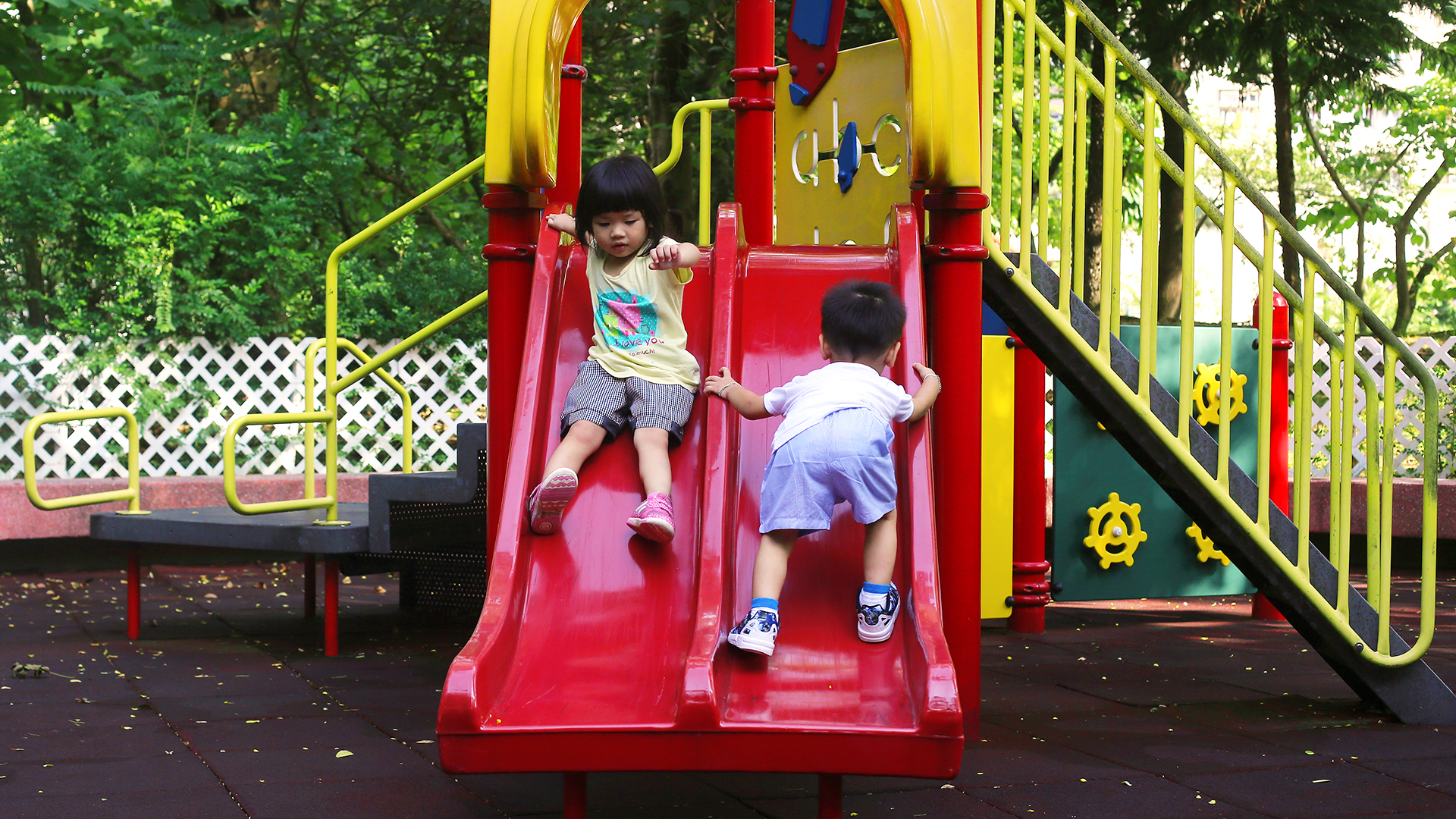 Two children play on a traditional playground