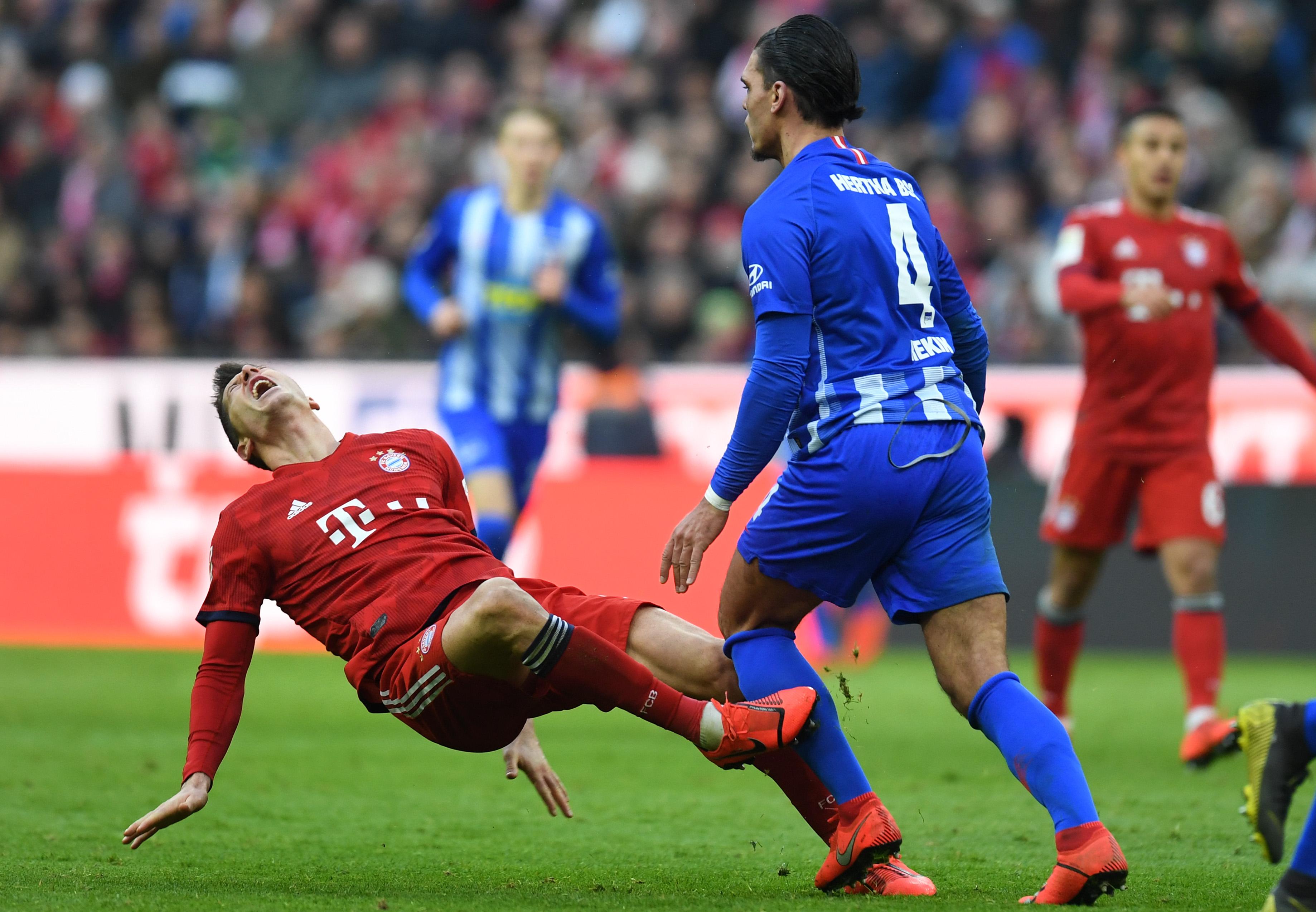 Bayern Munich's Polish striker Robert Lewandowski (L) falls after an attack of Berlin's midfielder Karim Rekik (R) during the German first division Bundesliga football match Bayern Munich vs Hertha Berlin in Munich on February 23, 2019.