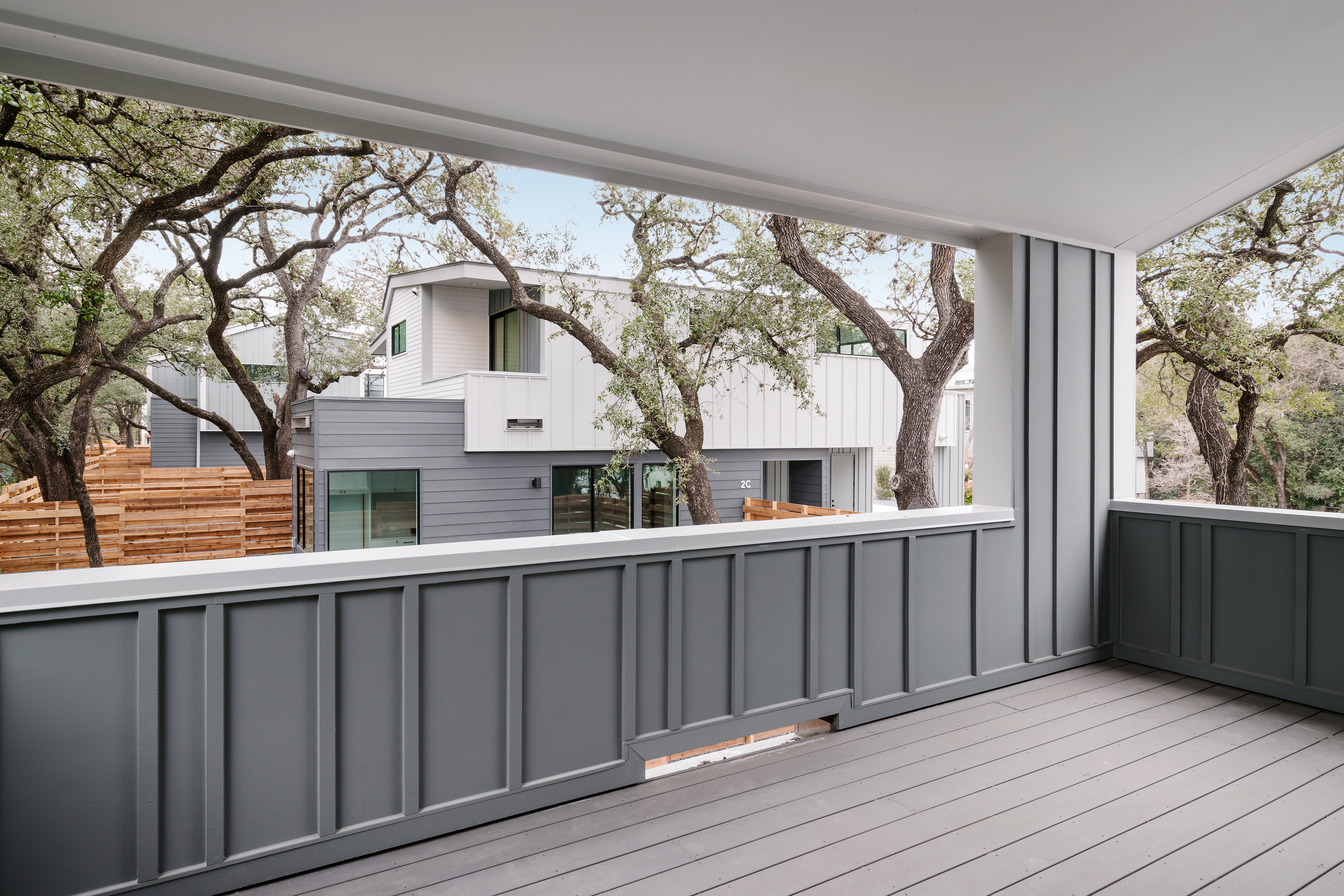 covered modern balcony looking out on trees and a nearby home by same architect