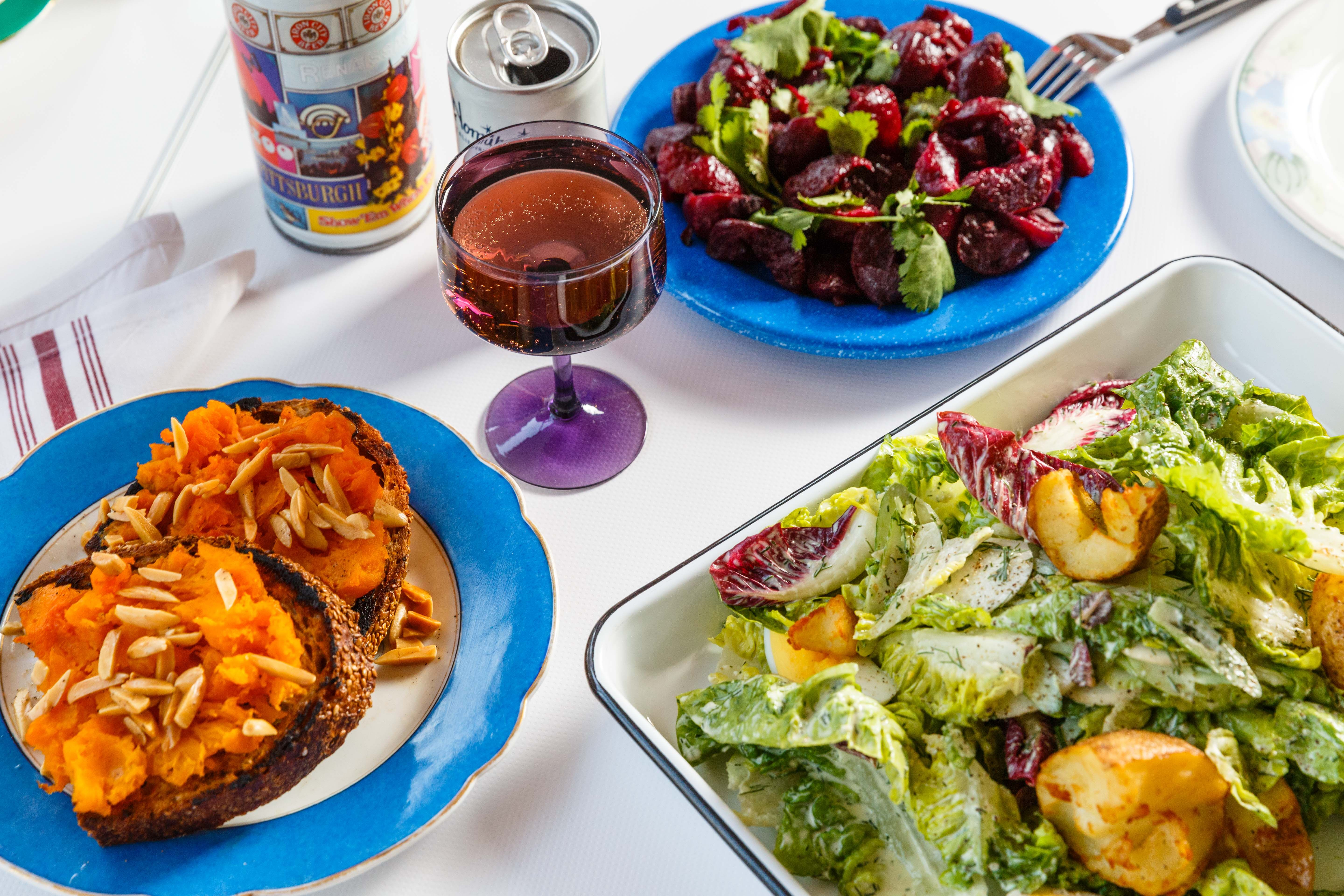 Squash toast and salad on colorful plates spread across a white table at Gertie