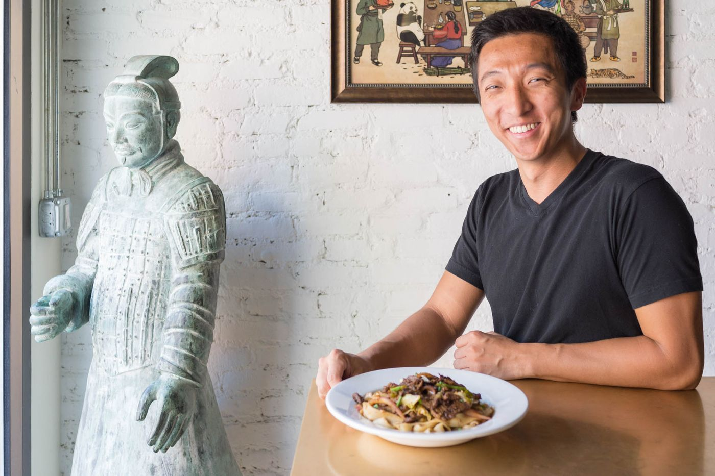 A man in a black v-neck t-shirt sits at a wooden table with a bowl of noodles in front of him. White brick is in the background.