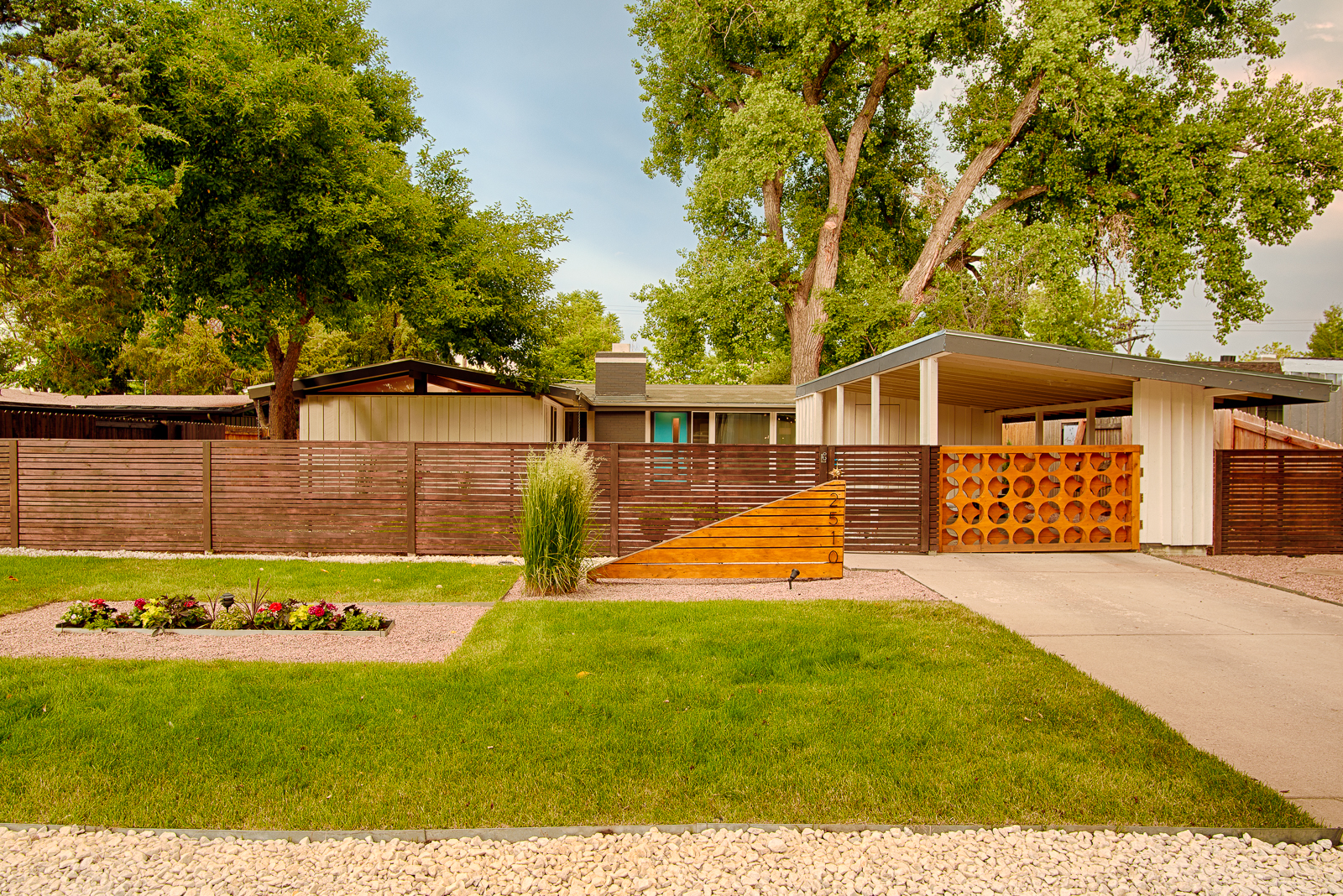 The exterior of a midcentury modern house. There is a wooden fence in front of the house. The house has an ivory facade. There is a green lawn in front.