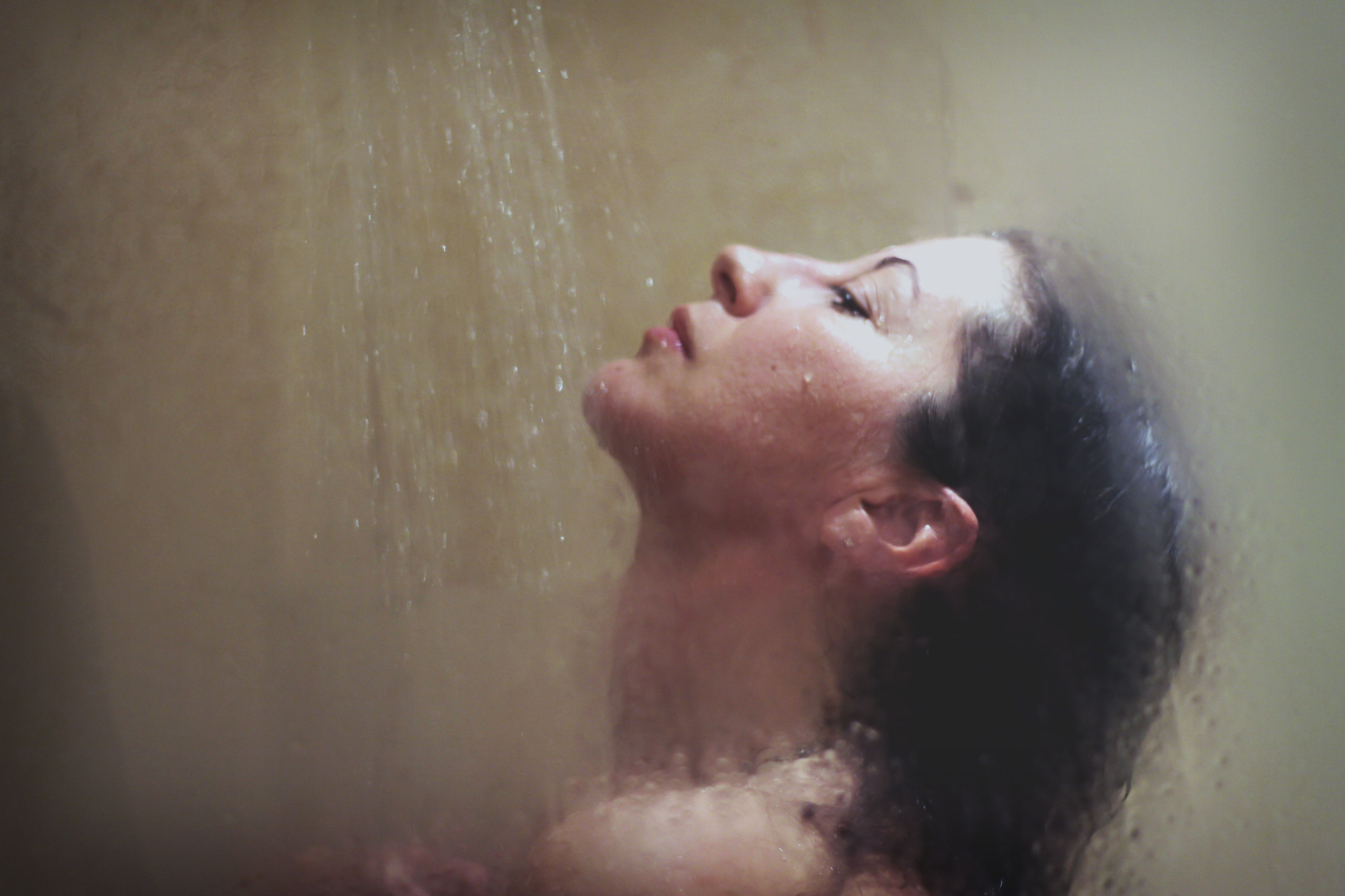 A woman from the neck up in the shower.