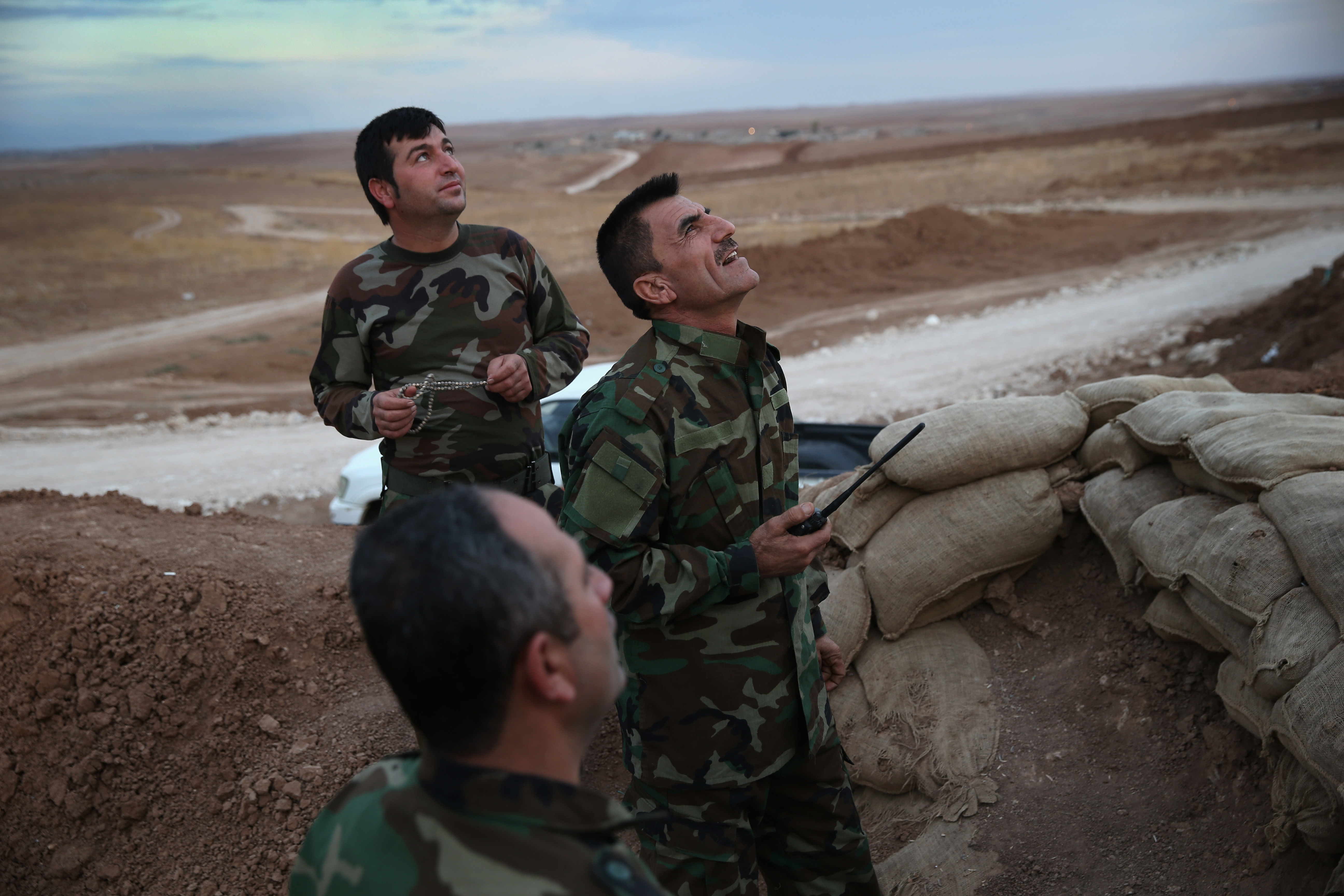 Camouflage-clad Kurdish forces in northern Iraq stand in a foxhole and look toward the sky.