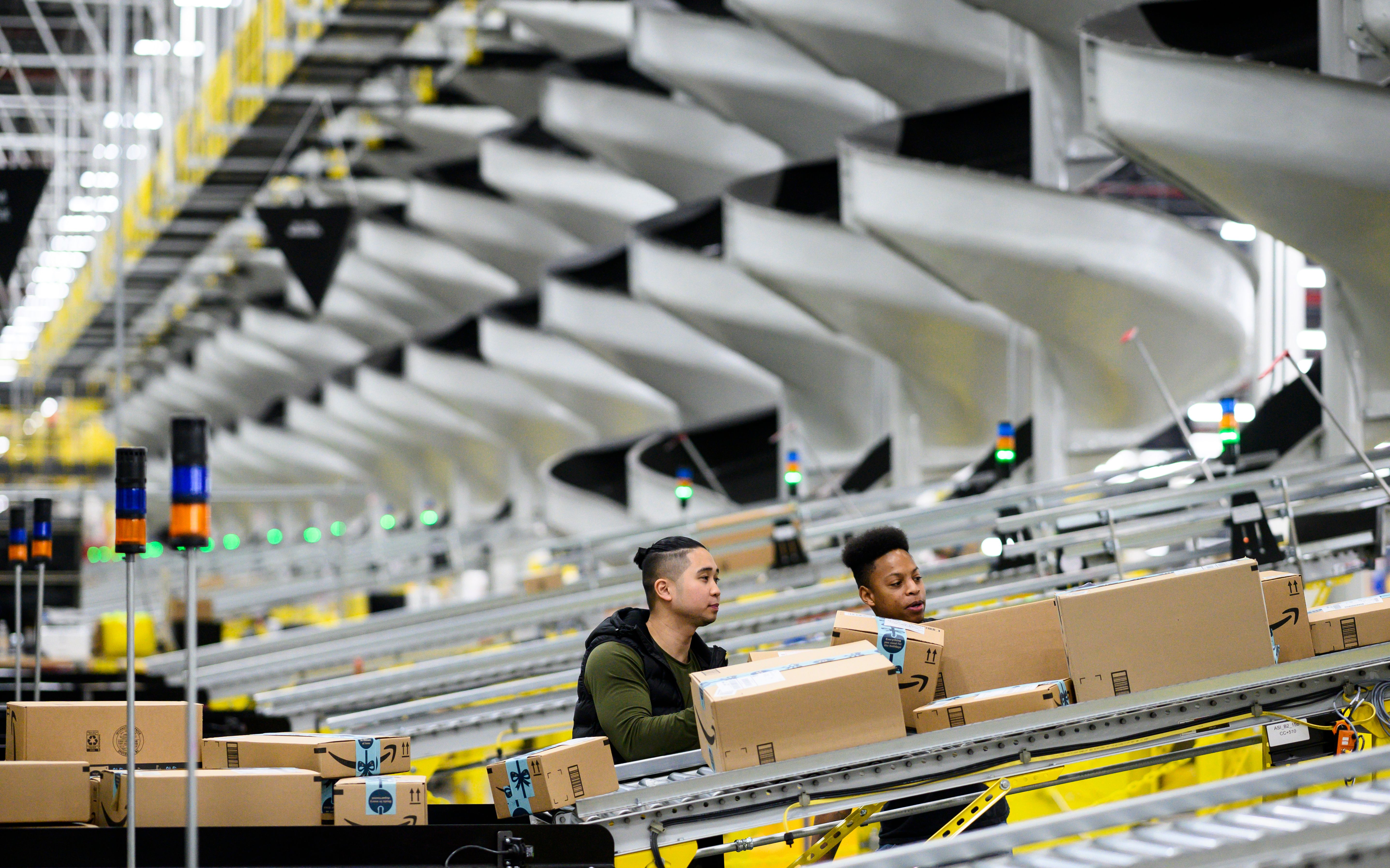 Two men working at an Amazon fulfillment center check the boxes moving down a conveyor belt.