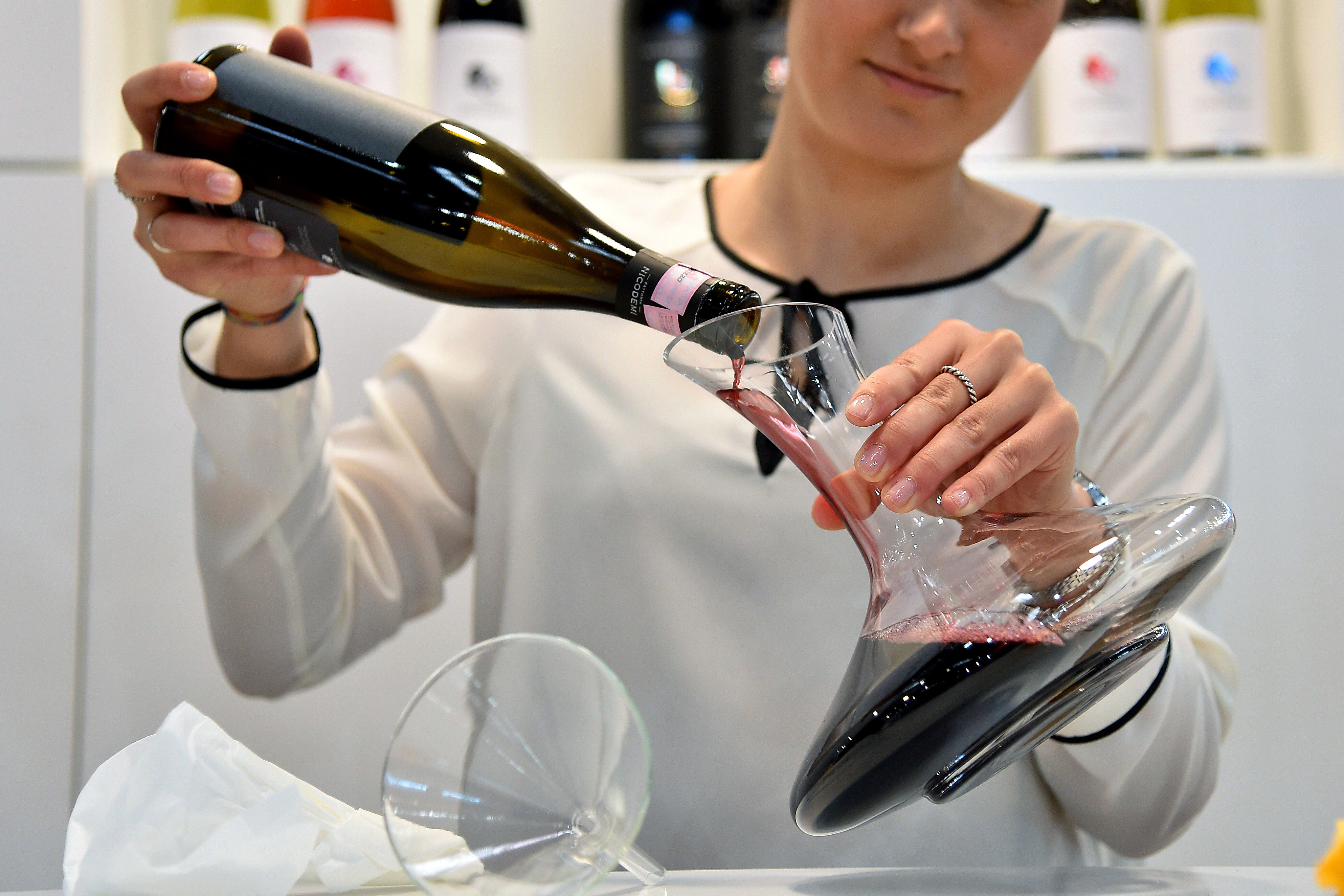 Woman pouring wine into a decanter