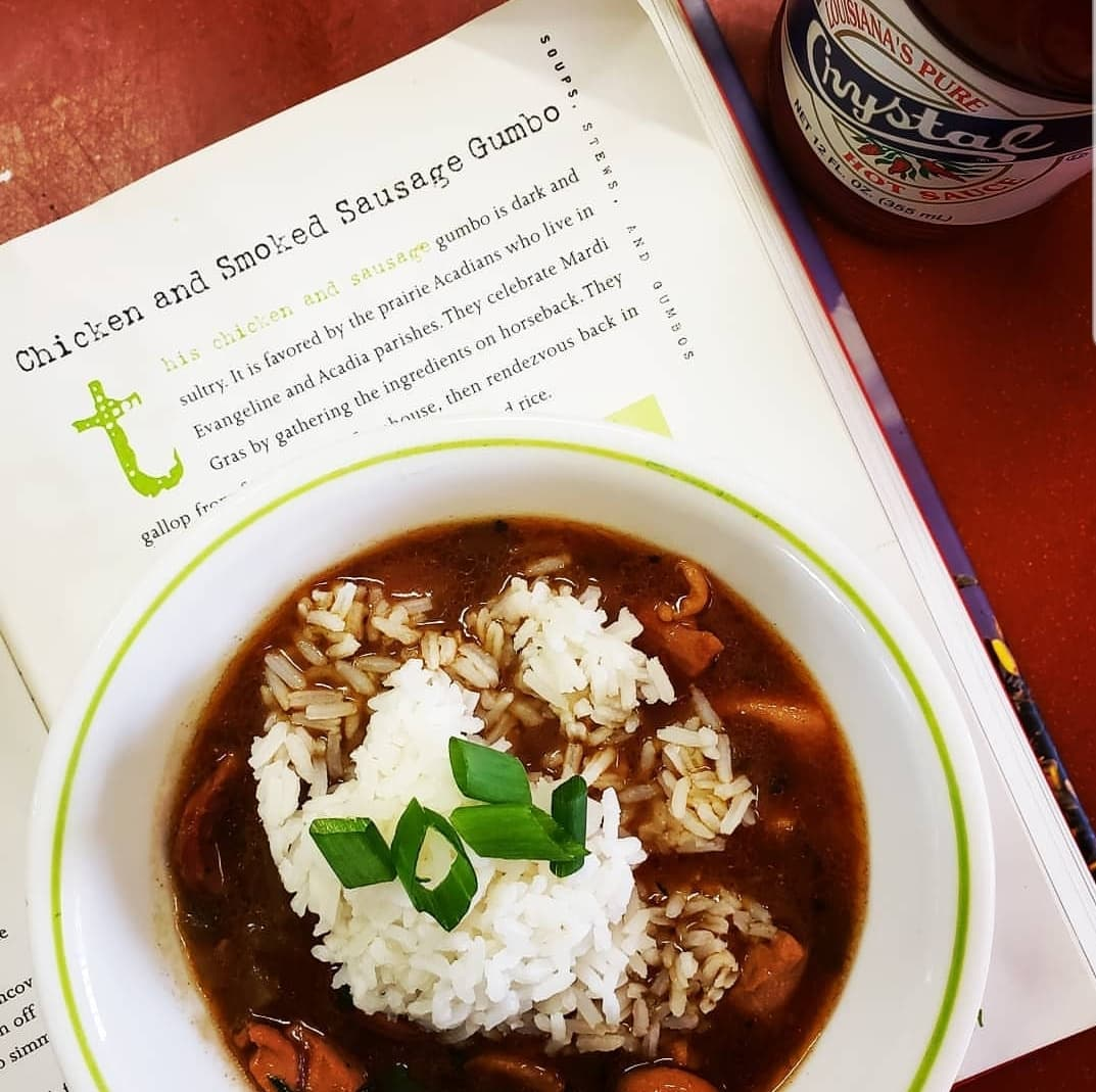 A bowl of gumbo on a cookbook.