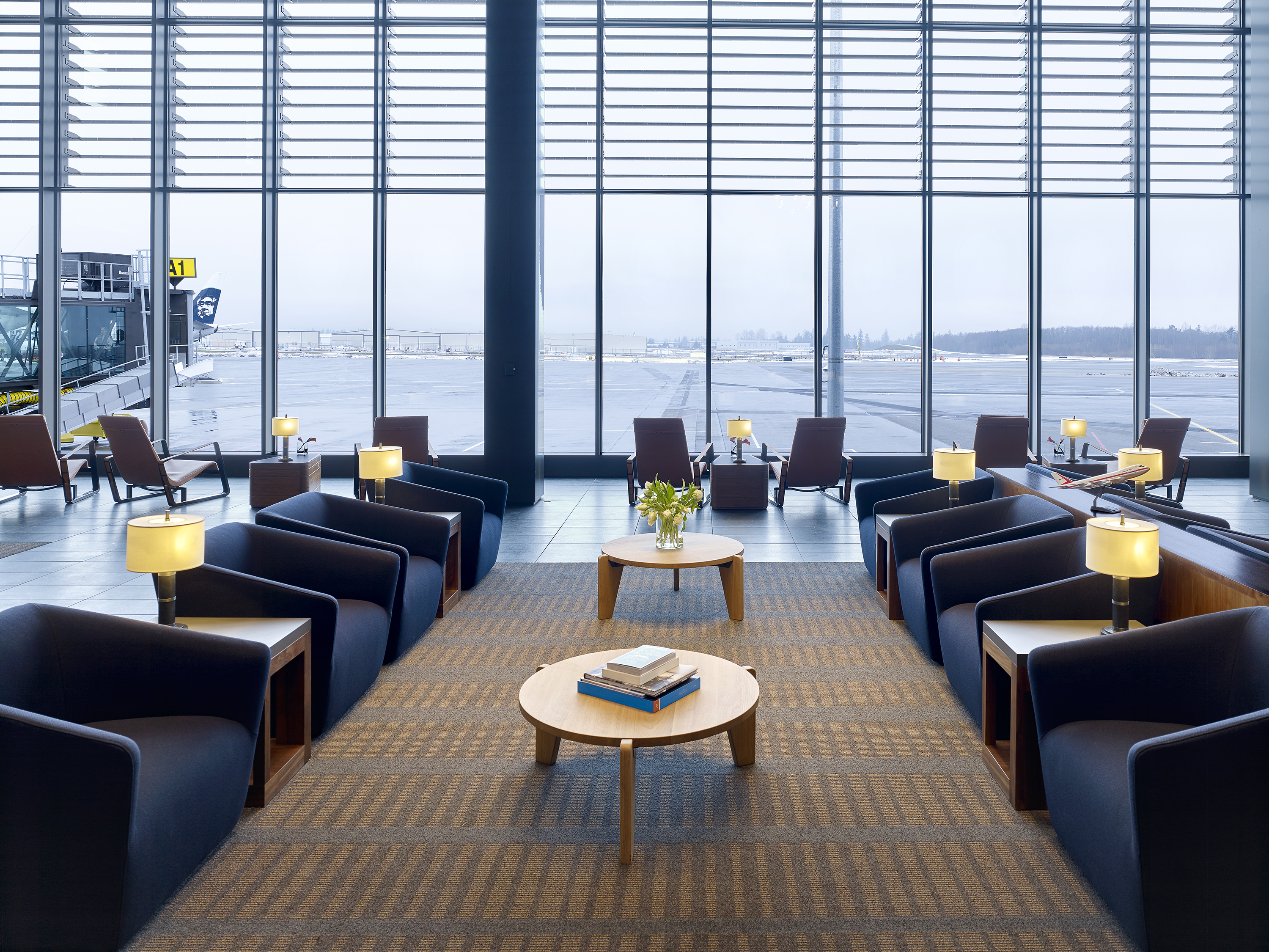 The interior of Paine Field Airport in Seattle. There are chairs, tables, and tall floor to ceiling windows overlooking a runway.