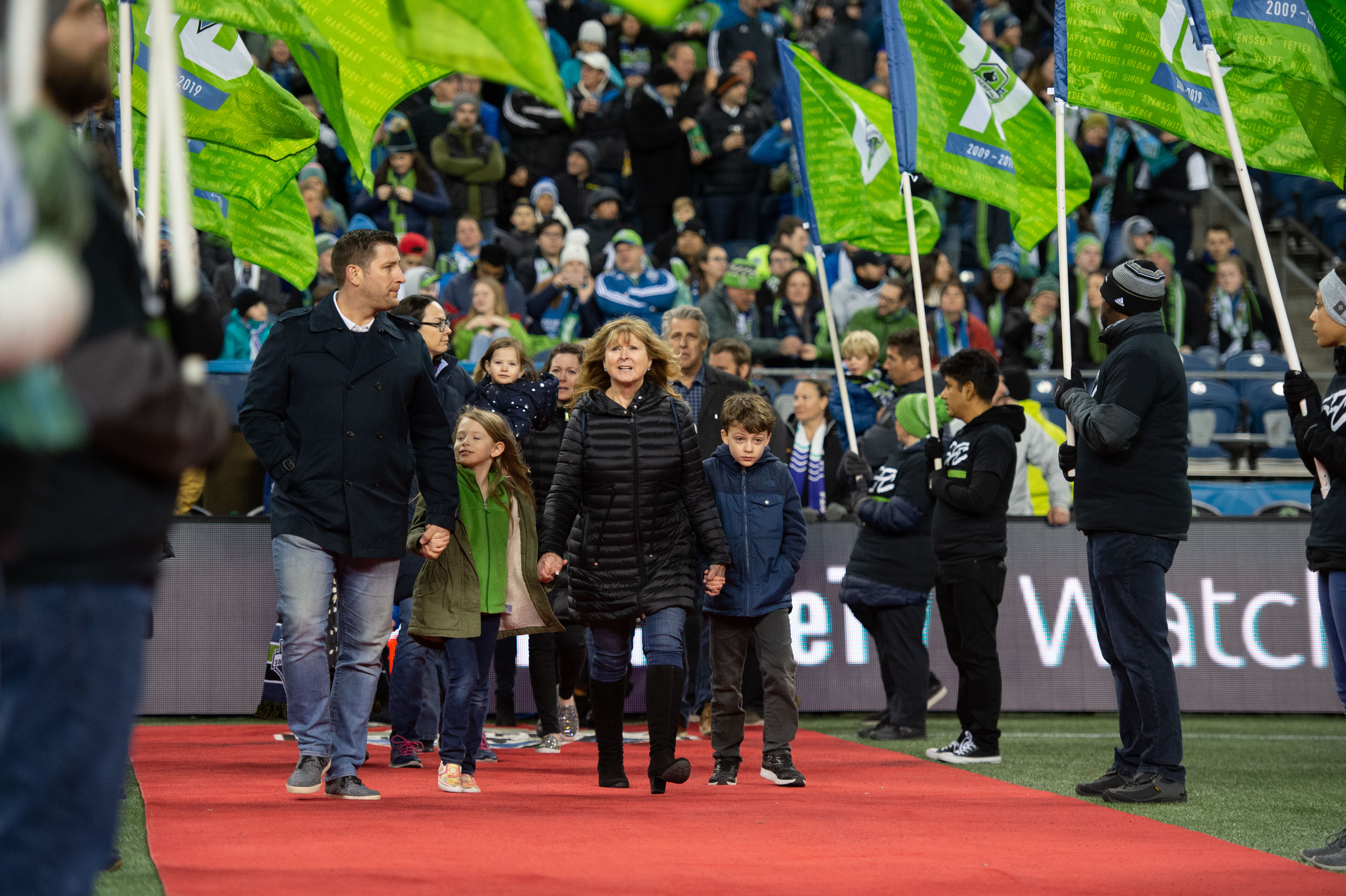 Sigi Schmid's surviving family marches through flags during the prematch ceremony.