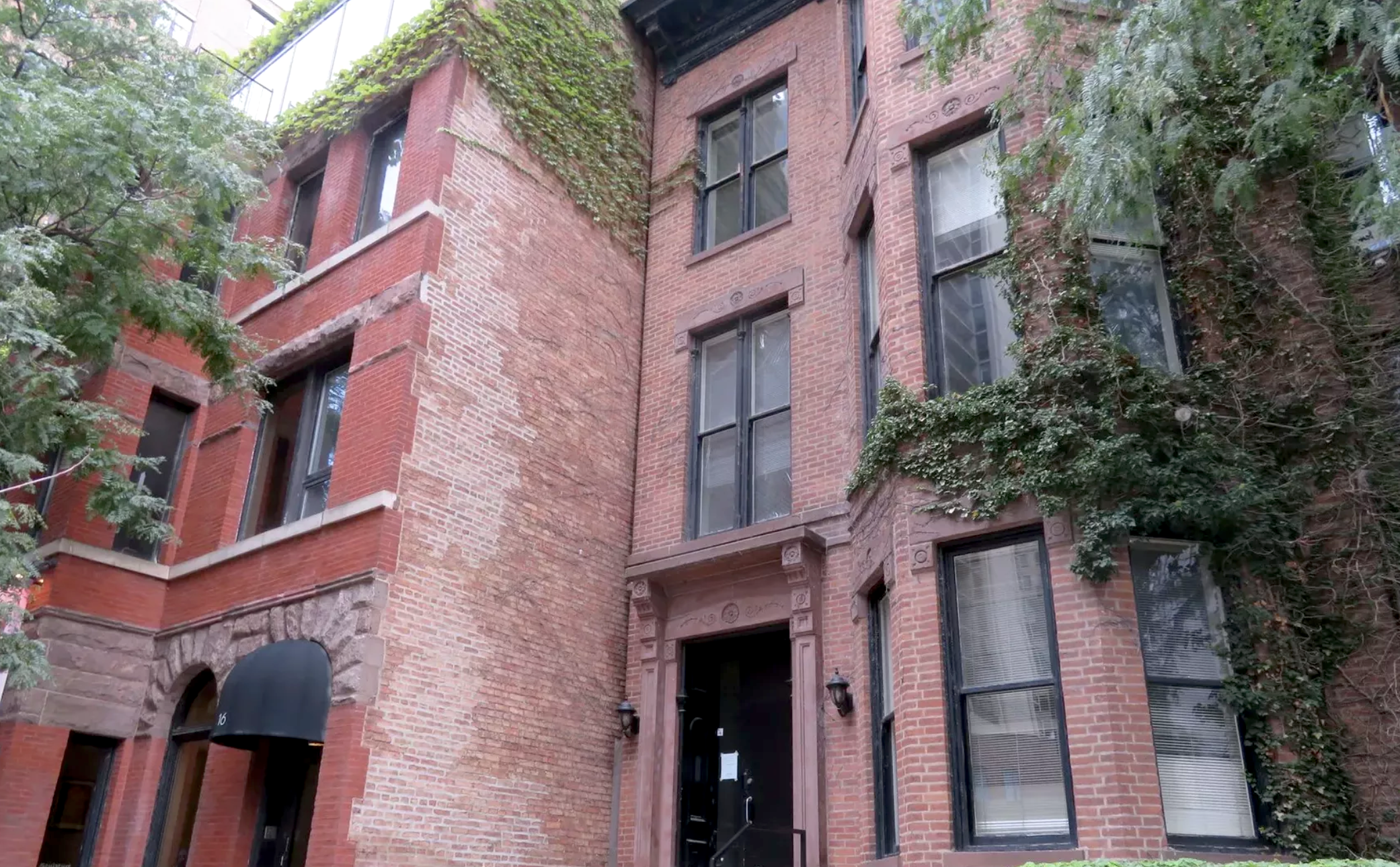 A red four-story brick row house covered by ivy.