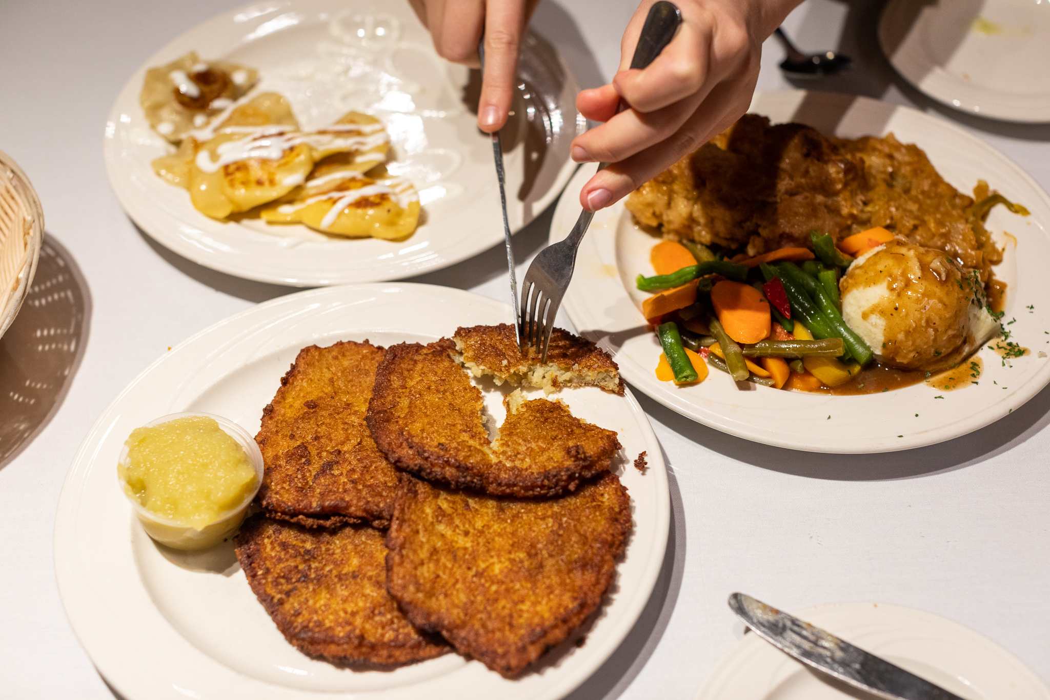 A pair of white hands use a fork and knife to slice off a piece of potato pancake on a plate with apple sauce. It's surrounded by plates of pierogi and city chicken with mashed potatoes and steamed veggies.