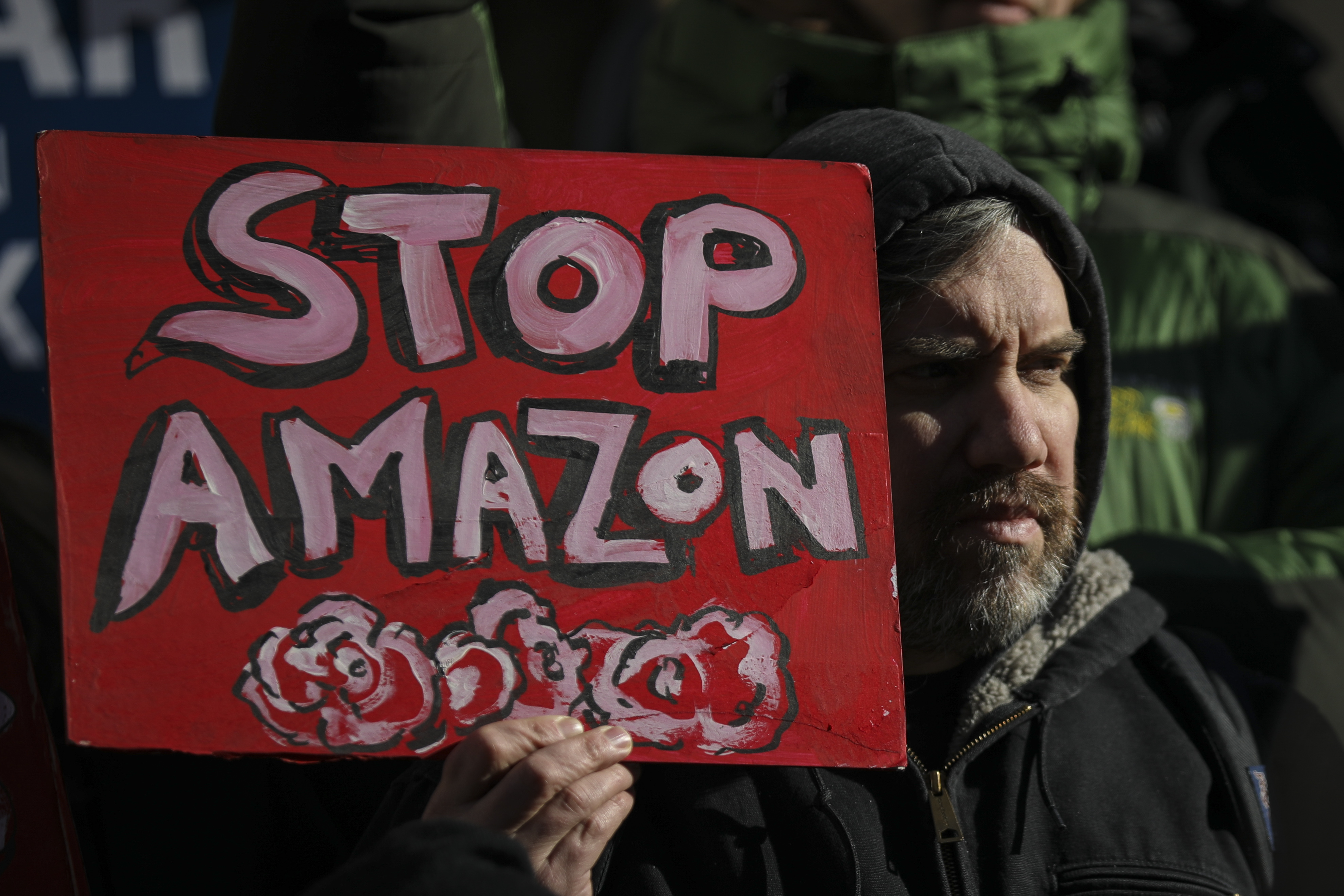 """An anti-Amazon protestors holds a sign reading """"Stop Amazon."""""""