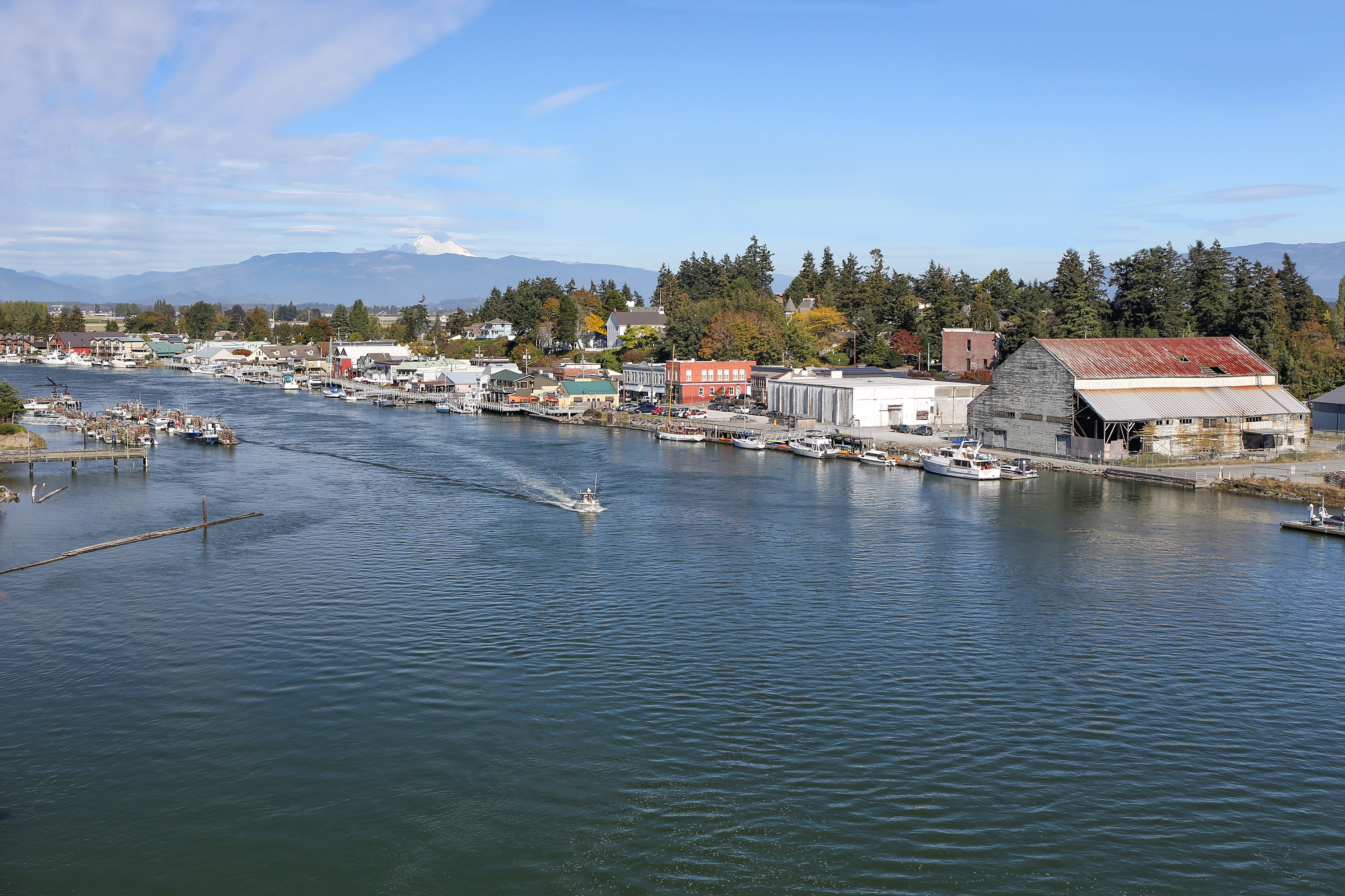 In the foreground is a body of water near Seattle. Lining the body of water are multiple houses and trees. In the distance are mountains.
