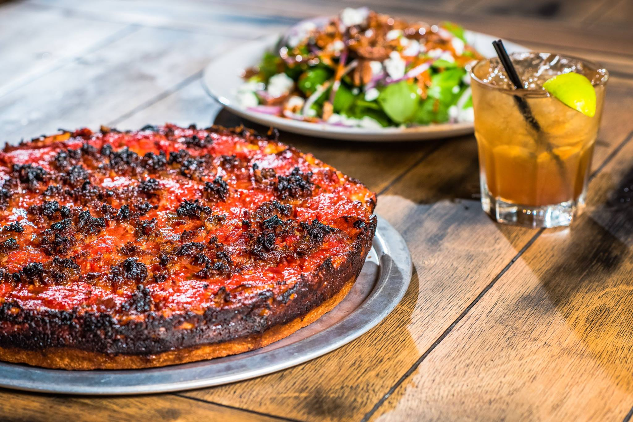 A view of a meaty Chicago deep dish-style pizza, with a cocktail and salad in the background.