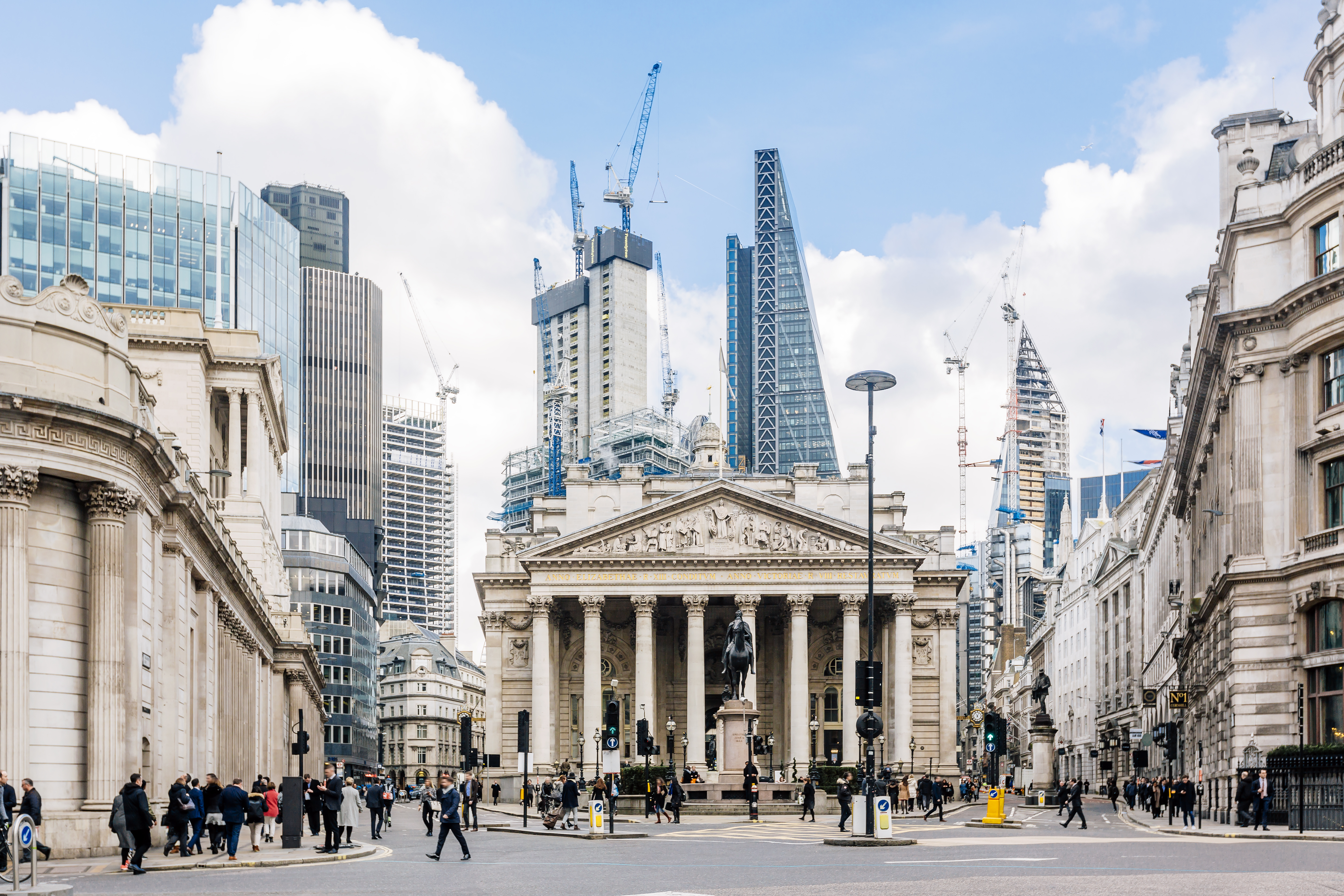 A street in London. There are various buildings lining the street. At the end of the street is a historic building with a domed roof and columns.