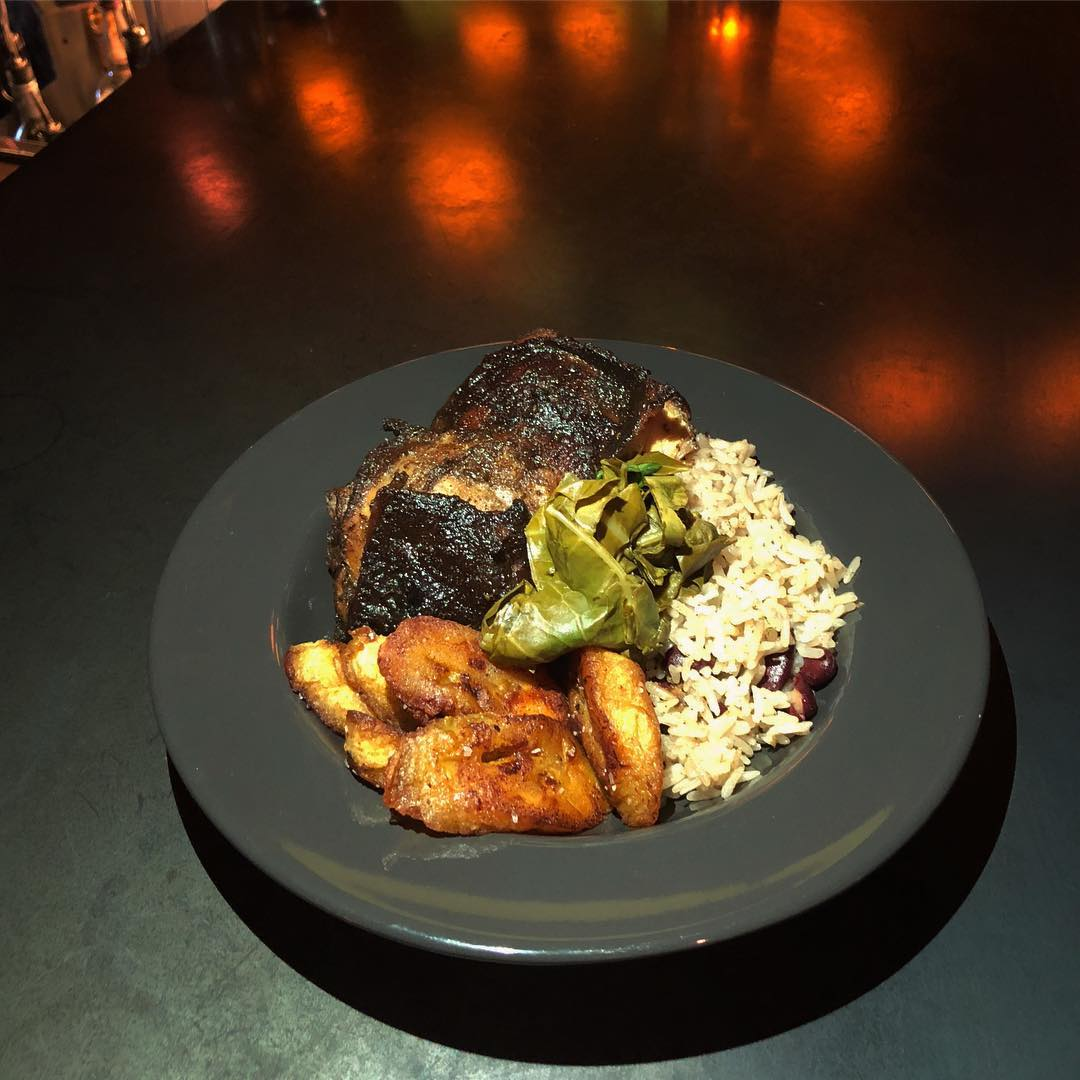 Jerk chicken thighs with pickled collard greens, coffee-glazed plantains, and rice and peas at Jammyland
