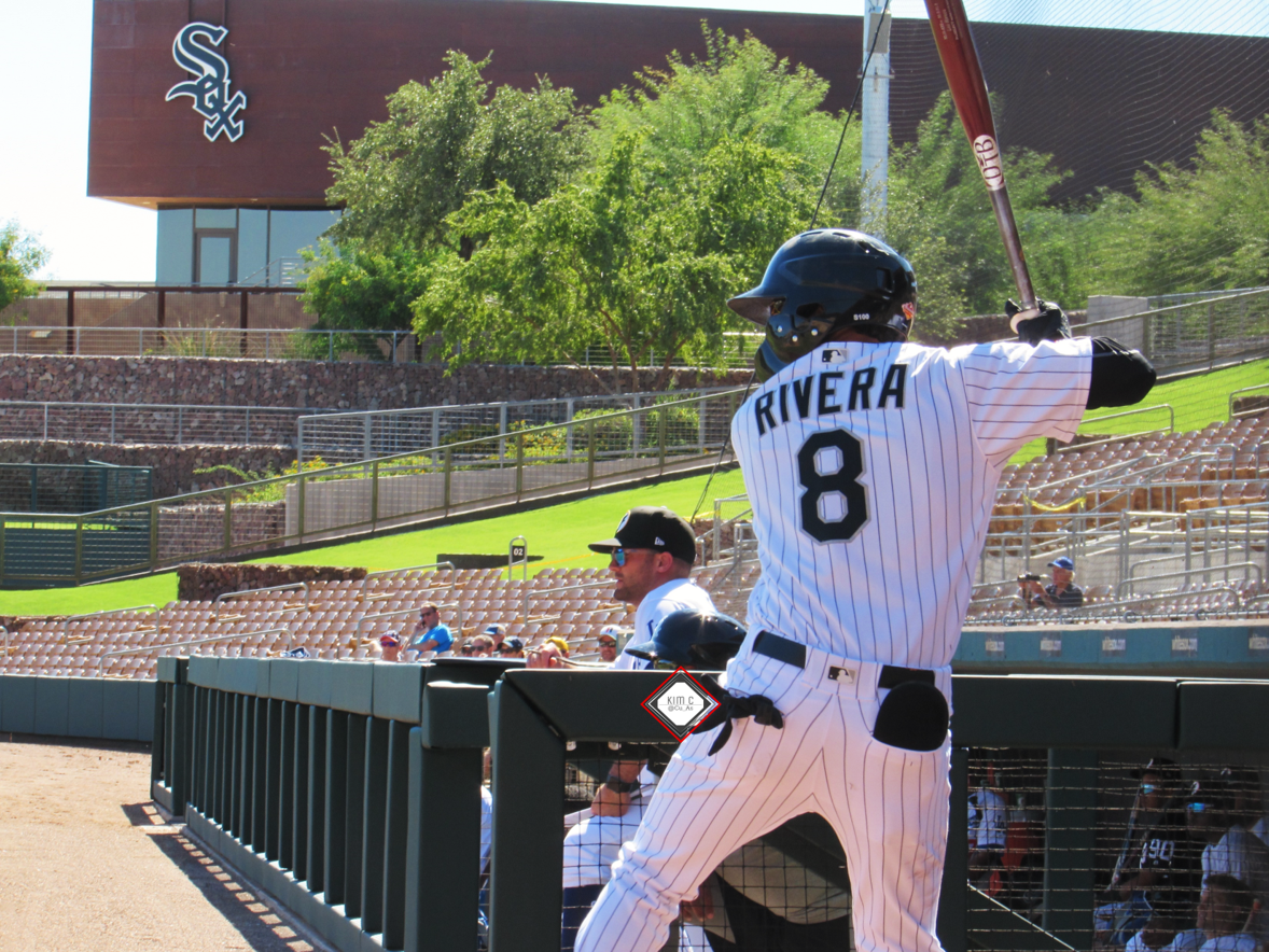 Laz Rivera batting with his back to the camera at the Sox spring training facility, a building with the Sox logo on it visible beyond right field