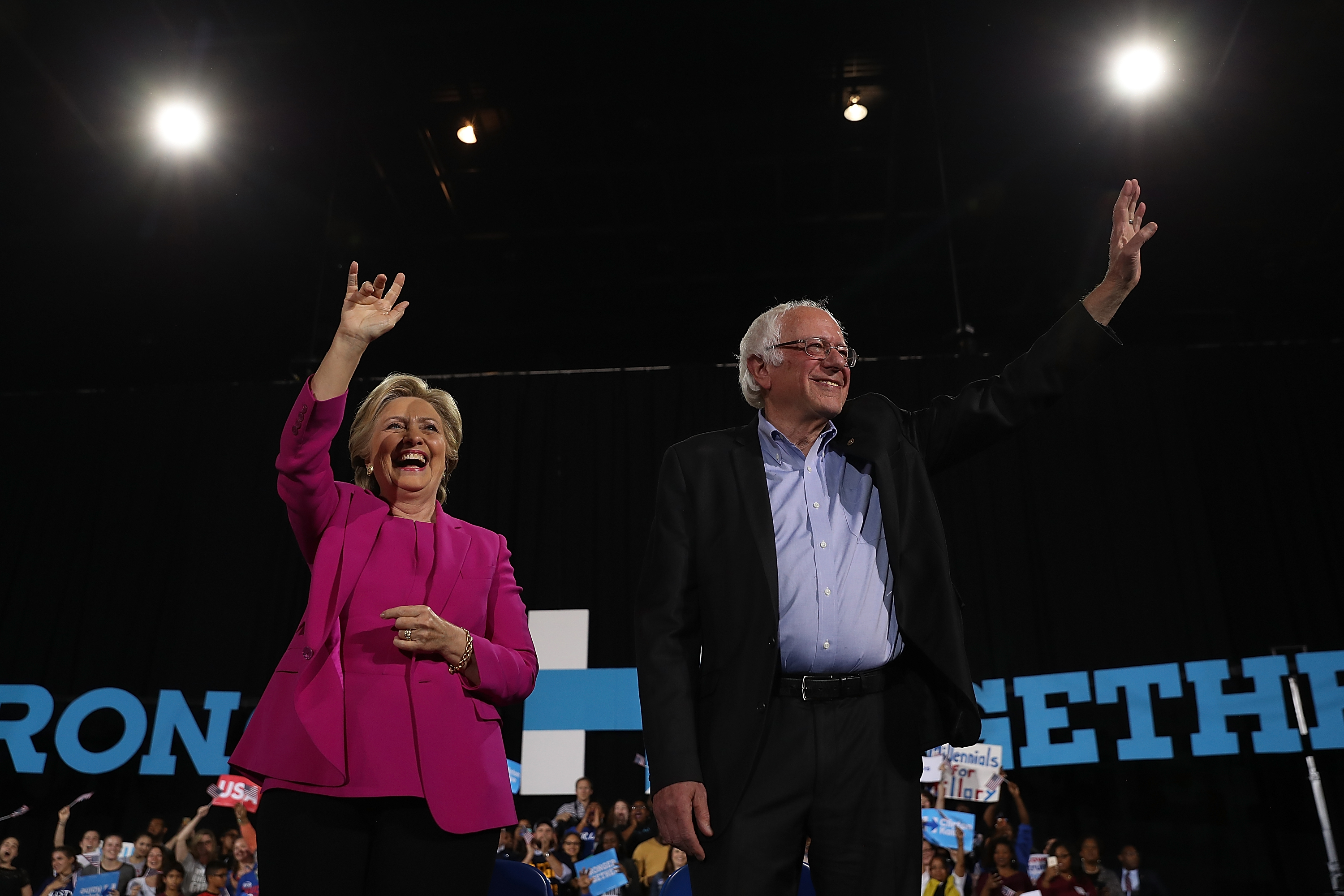 Hillary Clinton and Bernie Sanders stand on a stage and wave to the crowd.