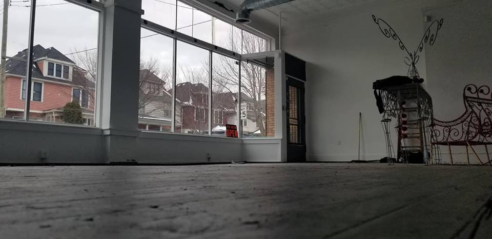 An empty room with a window looking out on Parker Street on a cloudy day.