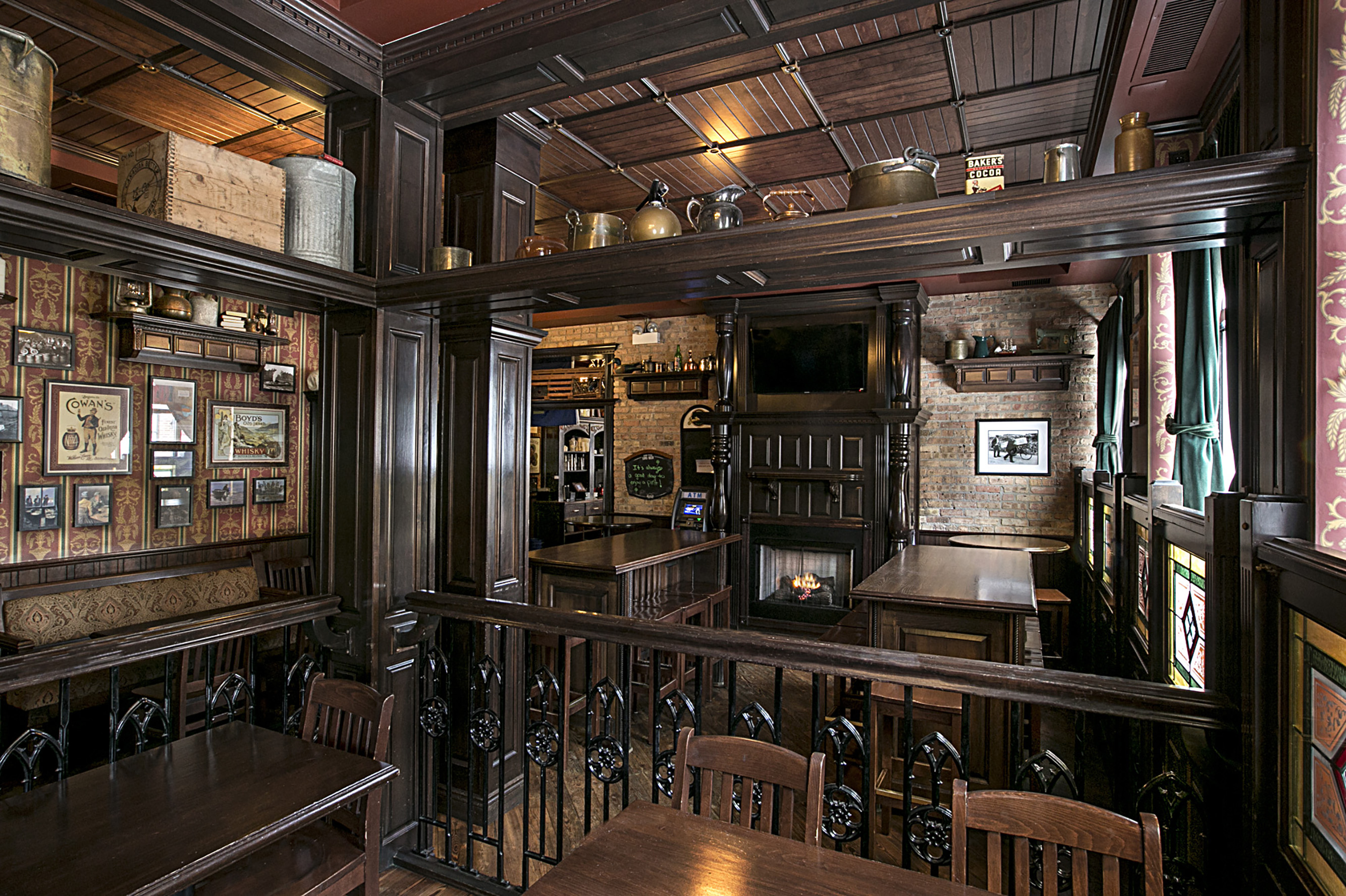 An interior shot of a dark wooded Irish bar. There are tables, chairs, and framed photos.