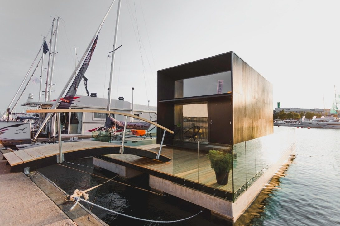 A floating tiny home at a pier with other boats. The tiny home has a rectangular shape and large windows.