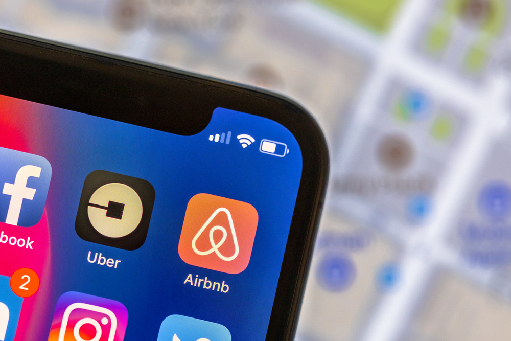 A phone screen displaying app icons for Airbnb and Uber.
