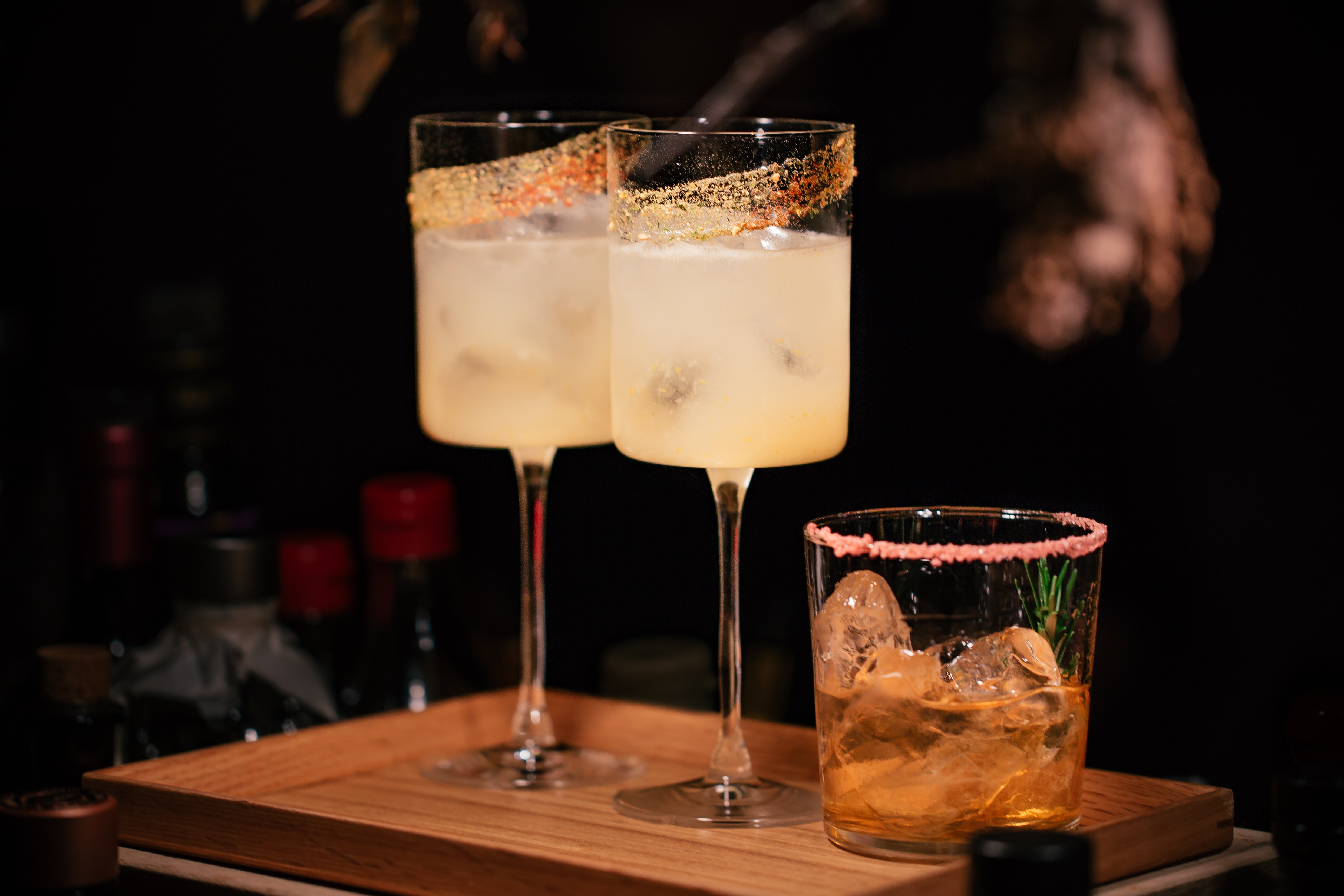 two tall cocktails in coupe glasses with one small cocktail next to it on a wood boards
