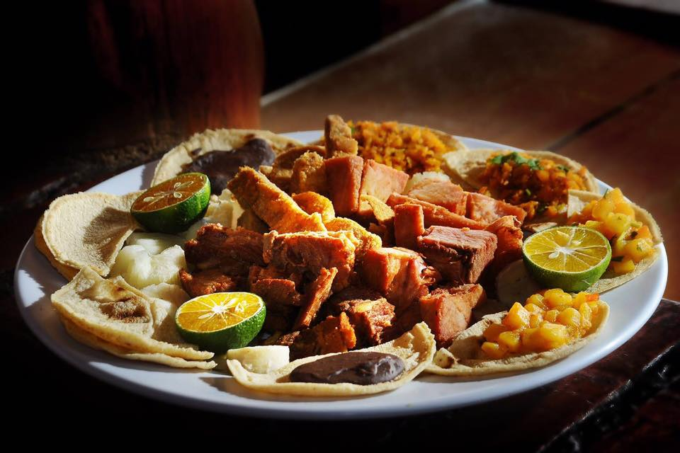 a platter of chicharrones tacos on a white plate