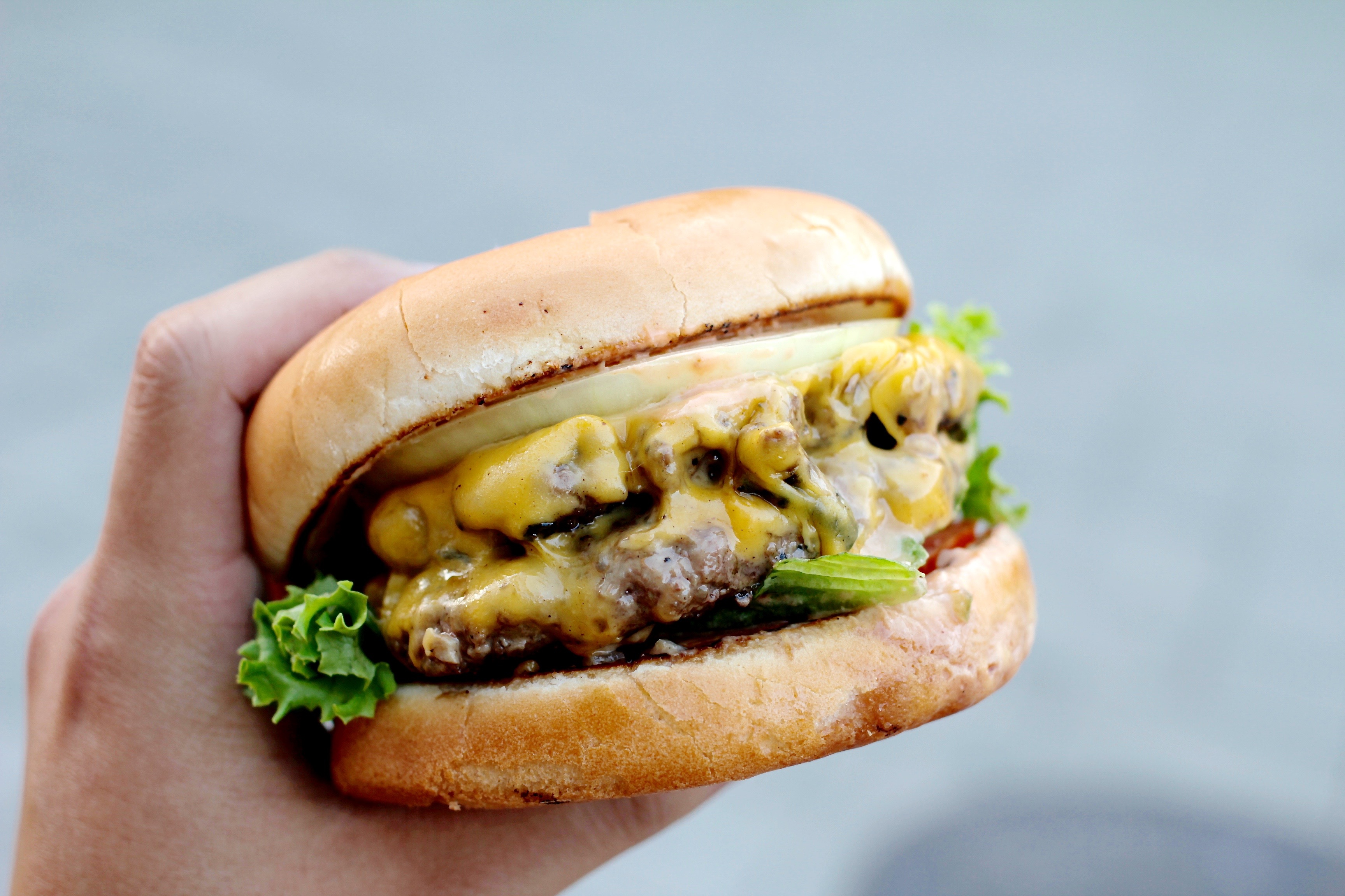 A hand holding a double-patty cheeseburger with thick onion on a gray background.
