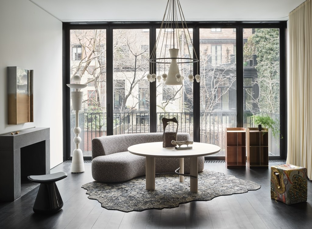 A living area with a couch, tables, fireplace, and floor to ceiling windows on one wall.