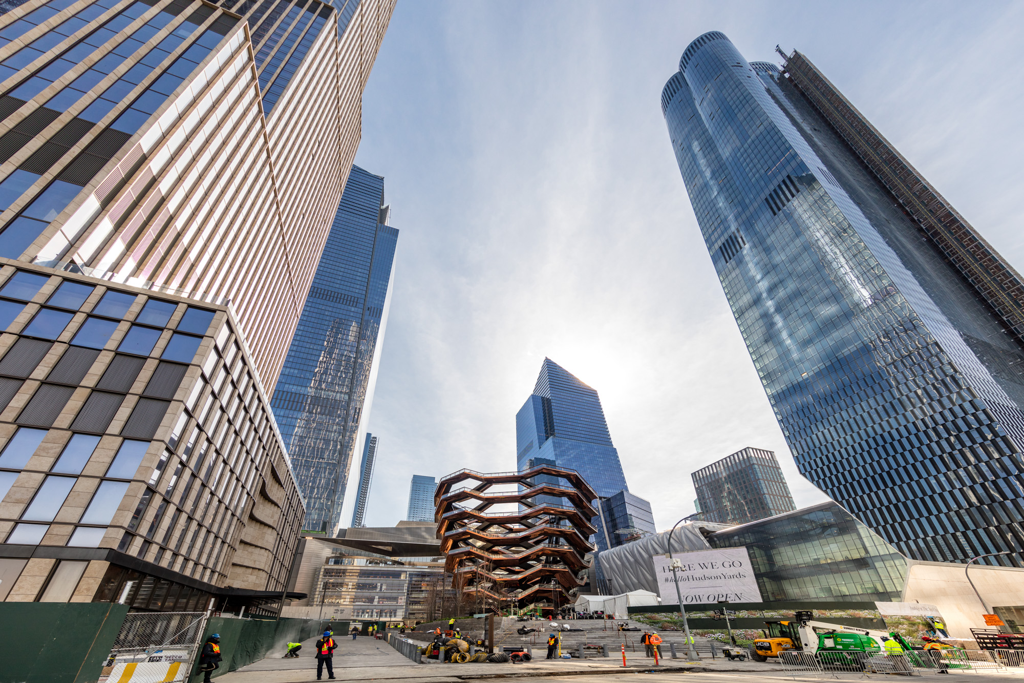Several tall buildings with glass facades surround a landmark that is shaped like a beehive and made from steel.