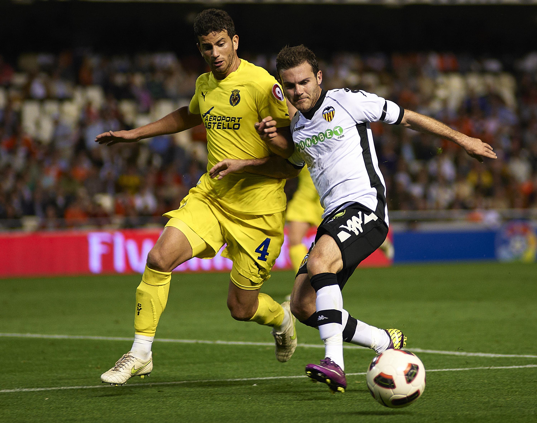 Mateo in 2011 against Valencia and Juan Mata