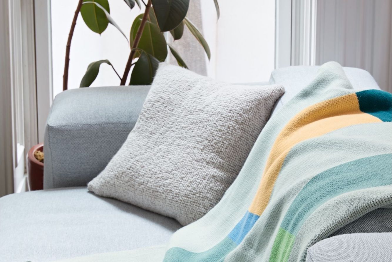 A colorful blanket rests on a gray sofa.