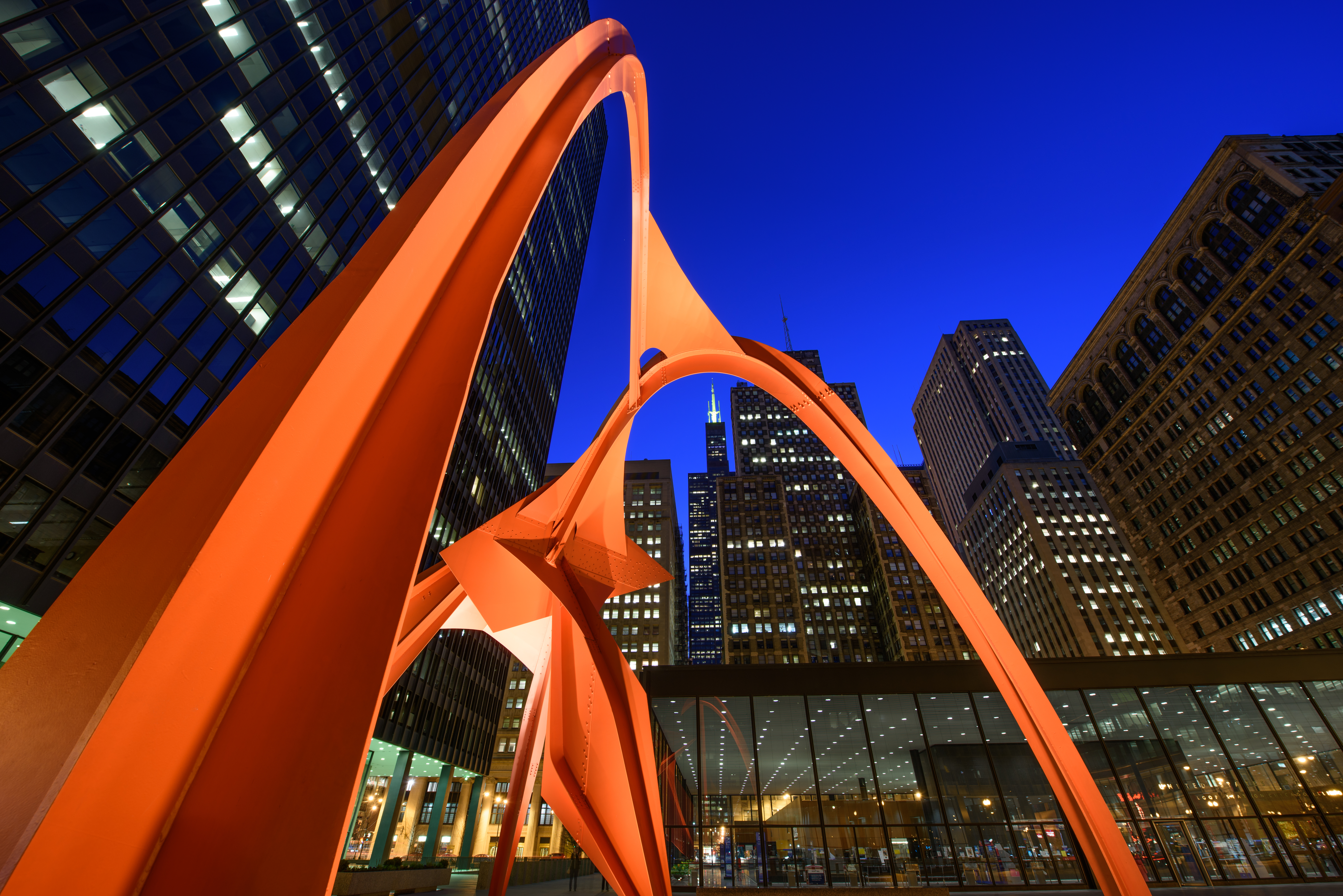 A public work of art in Chicago which is a tall curved orange metal structure near city buildings.