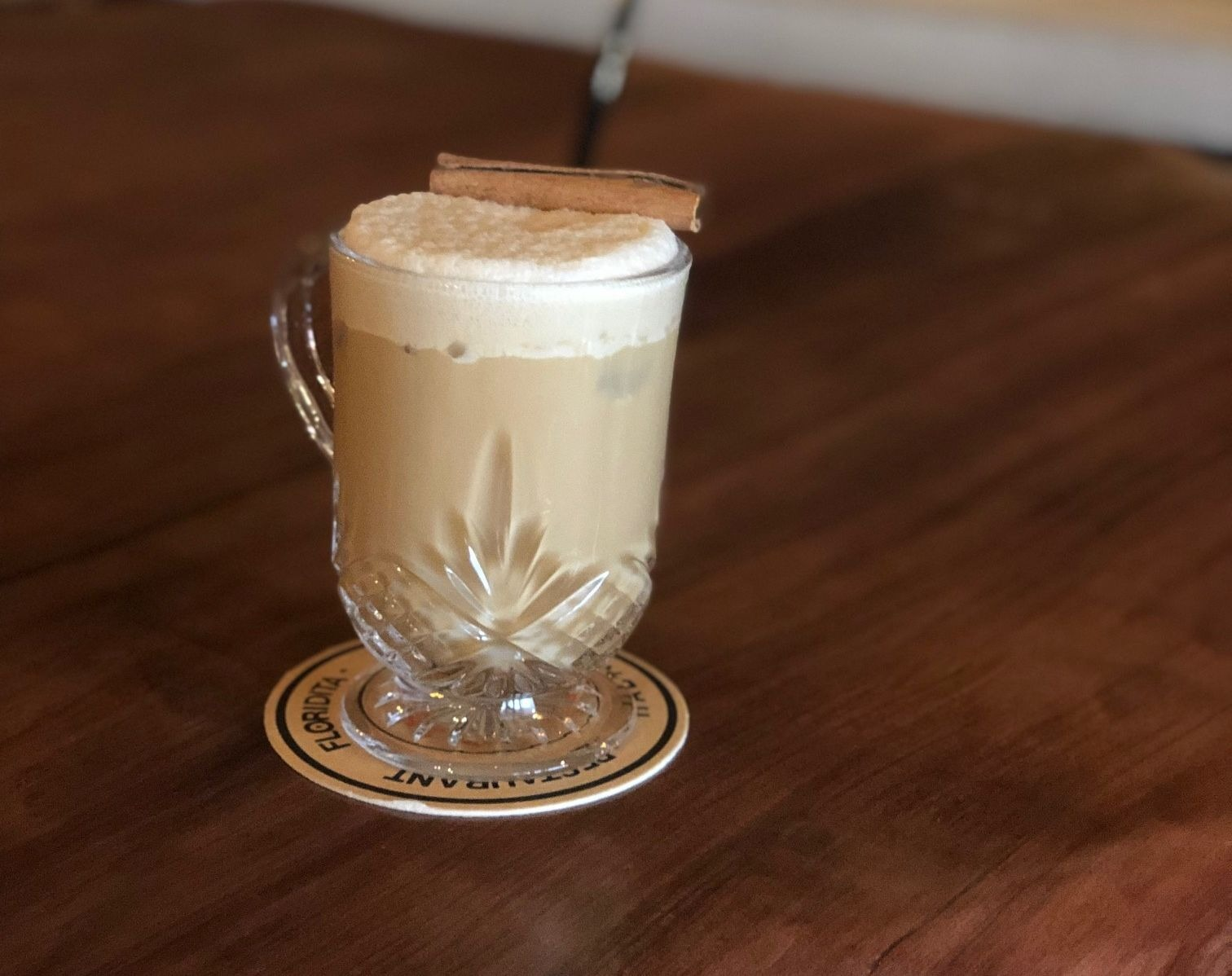 A beige cocktail with a foamy top and cinnamon stick garnish —the CoffeeCha at Gustazo in Cambridge —is shown here served in a glass mug on a wooden table