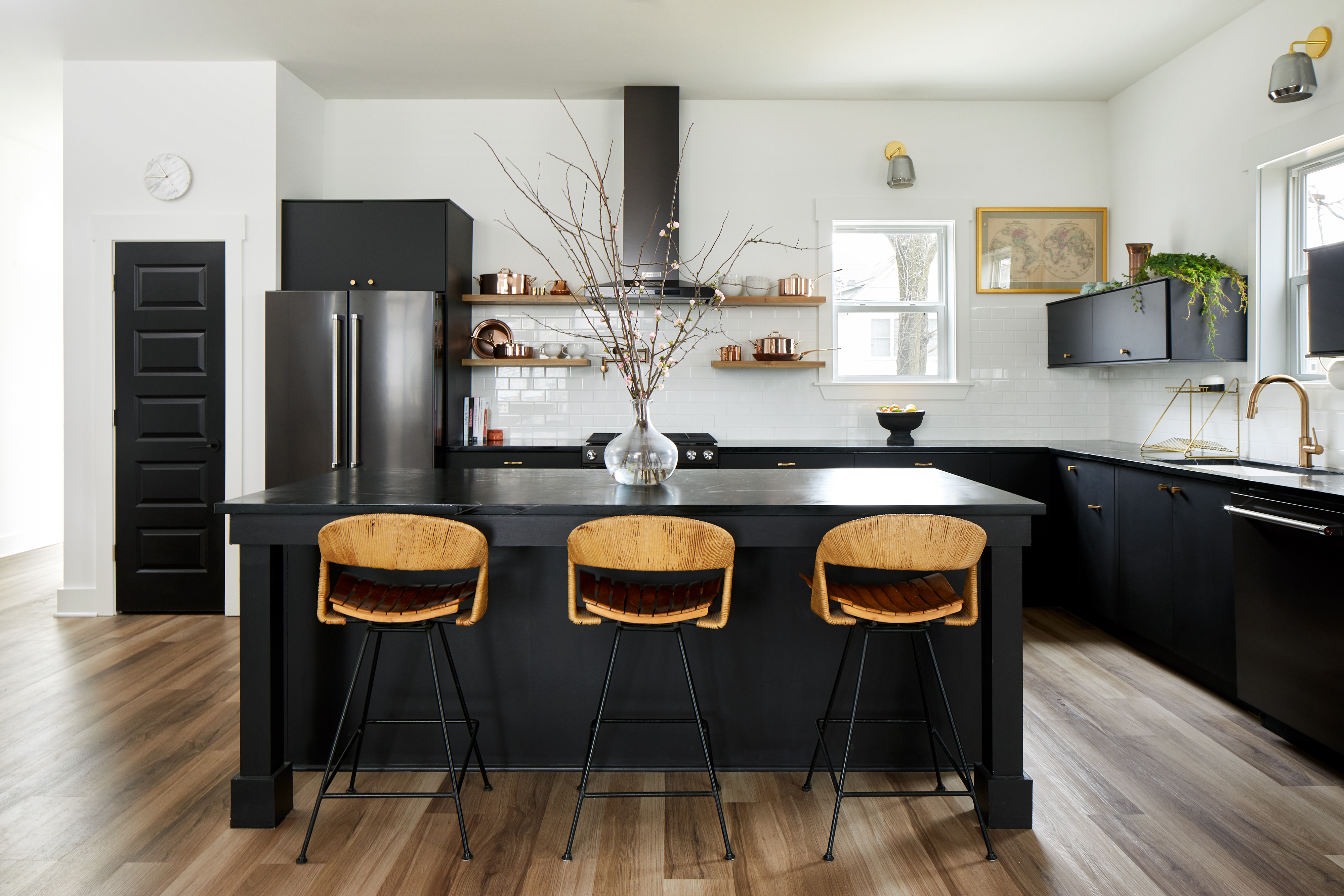 A kitchen with a wooden floor and a kitchen island with three chairs. The kitchen island and cabinets are painted black.
