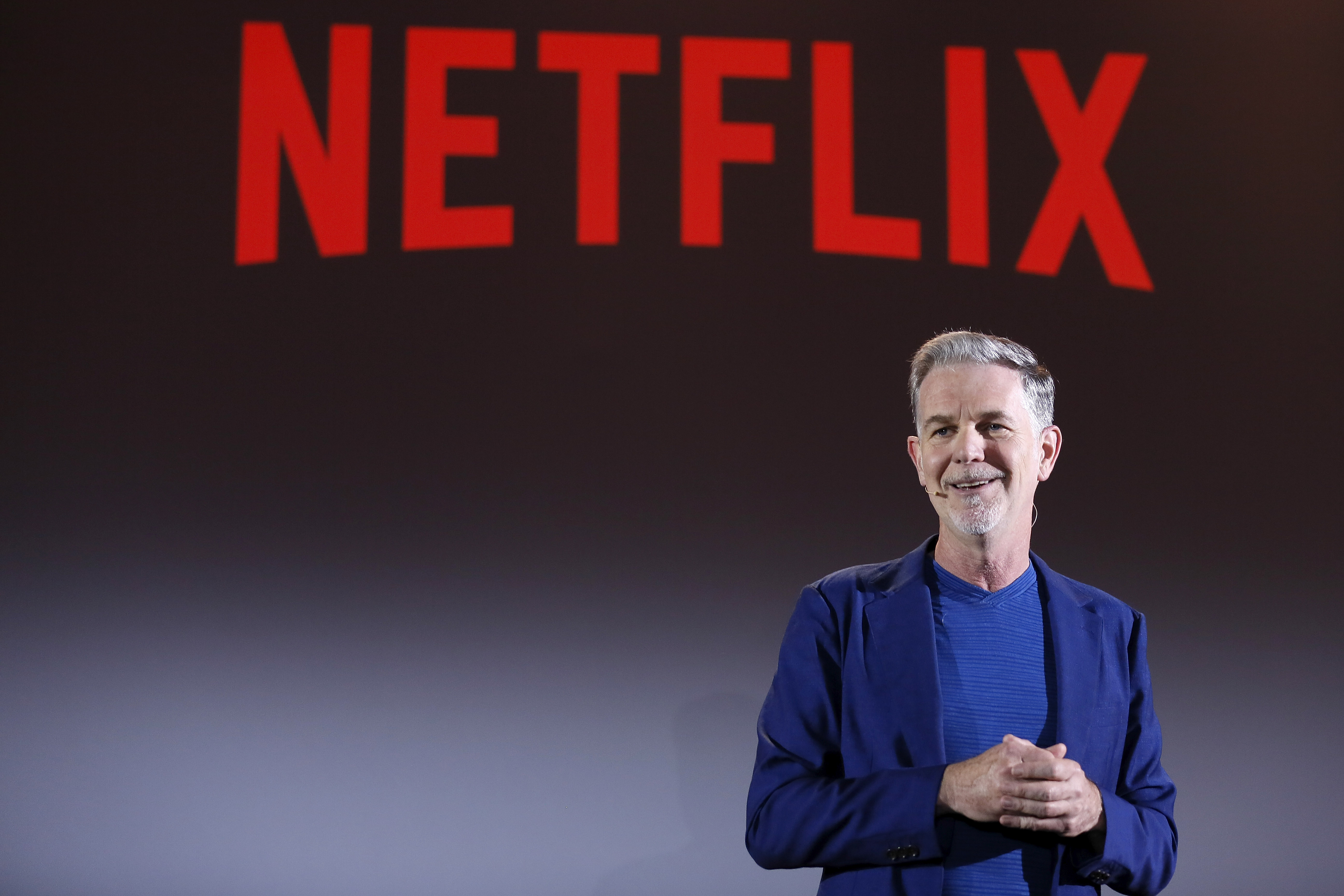 """Reed Hastings onstage in front of a sign reading """"Netflix."""""""