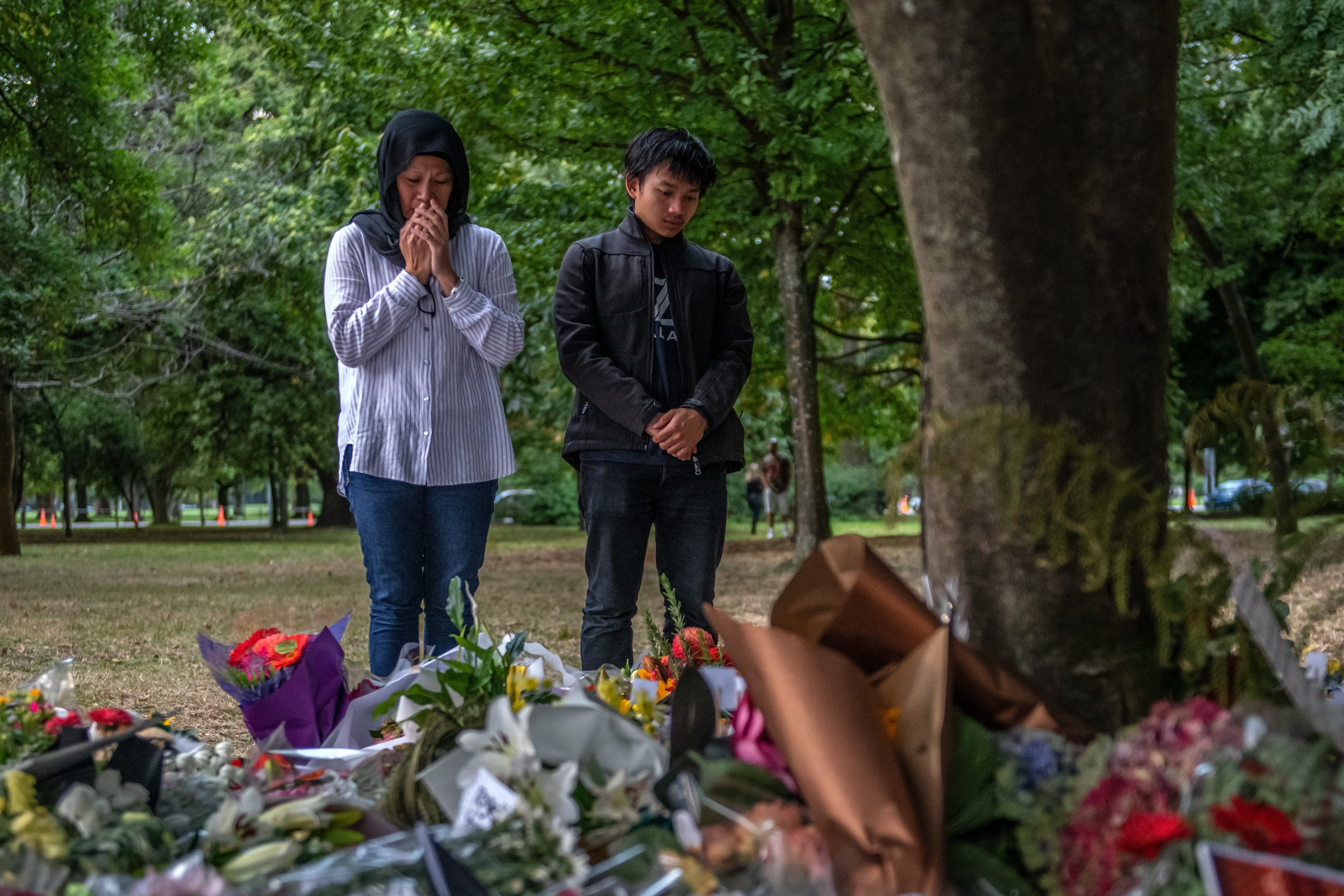 Two people stand at a memorial of piled bouquets of flowers in honor of the shooting victims in mosques in Christchurch, New Zealand.