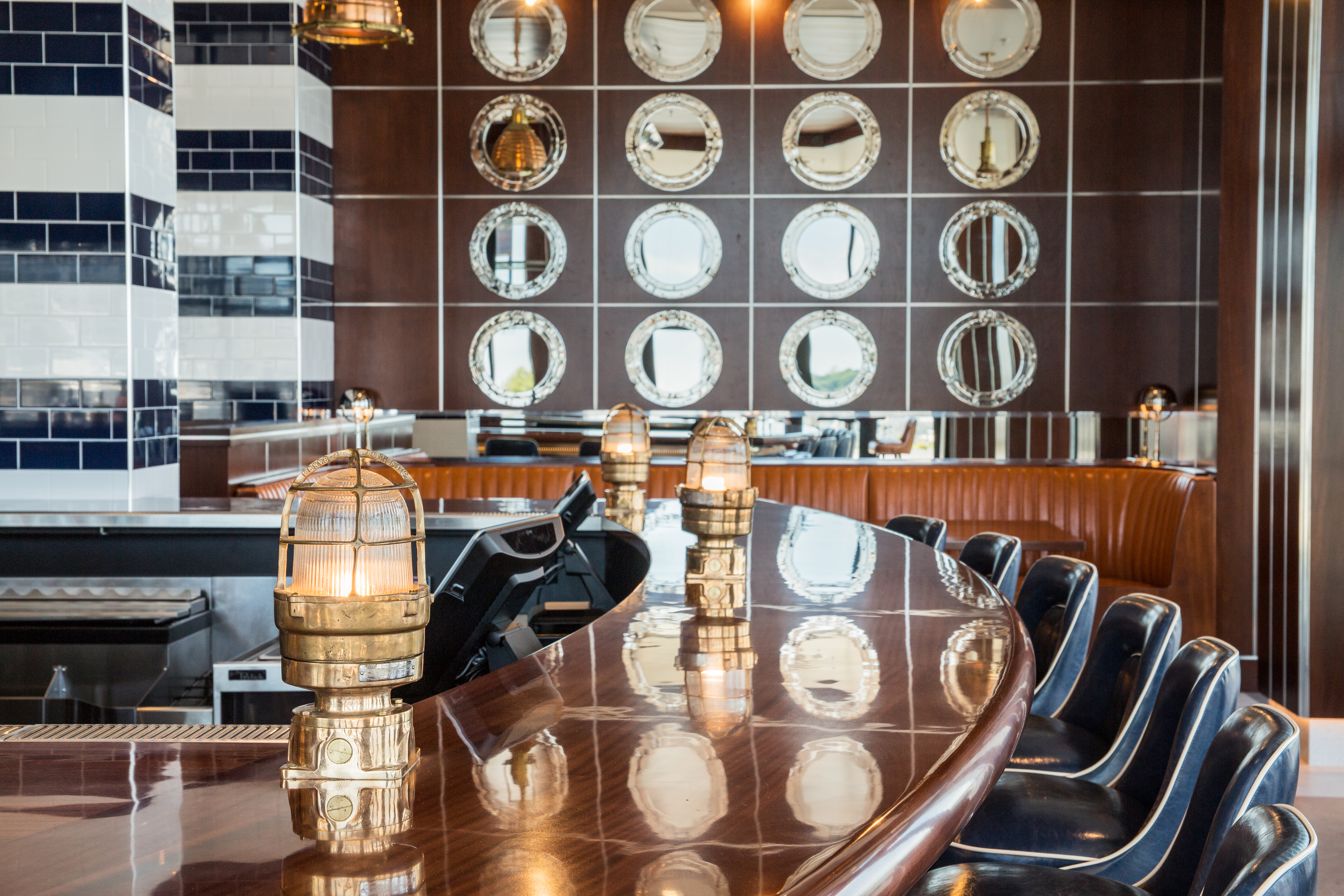 A curved wooden bar at ReelHouse Marina Bay arcs towards the rear of the frame, with blue barstools in alignment and porthole-shaped mirrors adorning the wall in the back