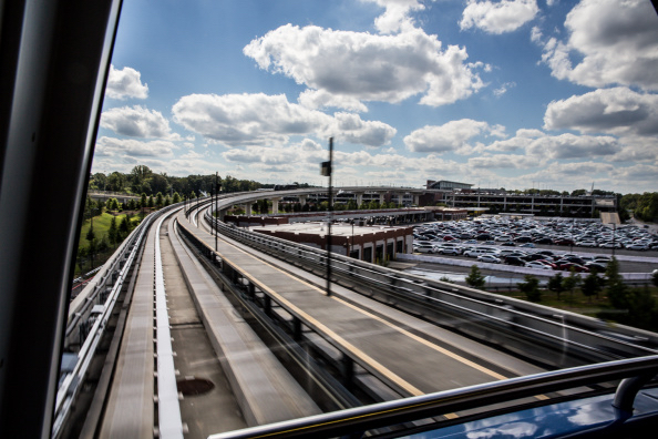 The view from the front car of a MARTA train, looking down the tracks that hang over parking lots.