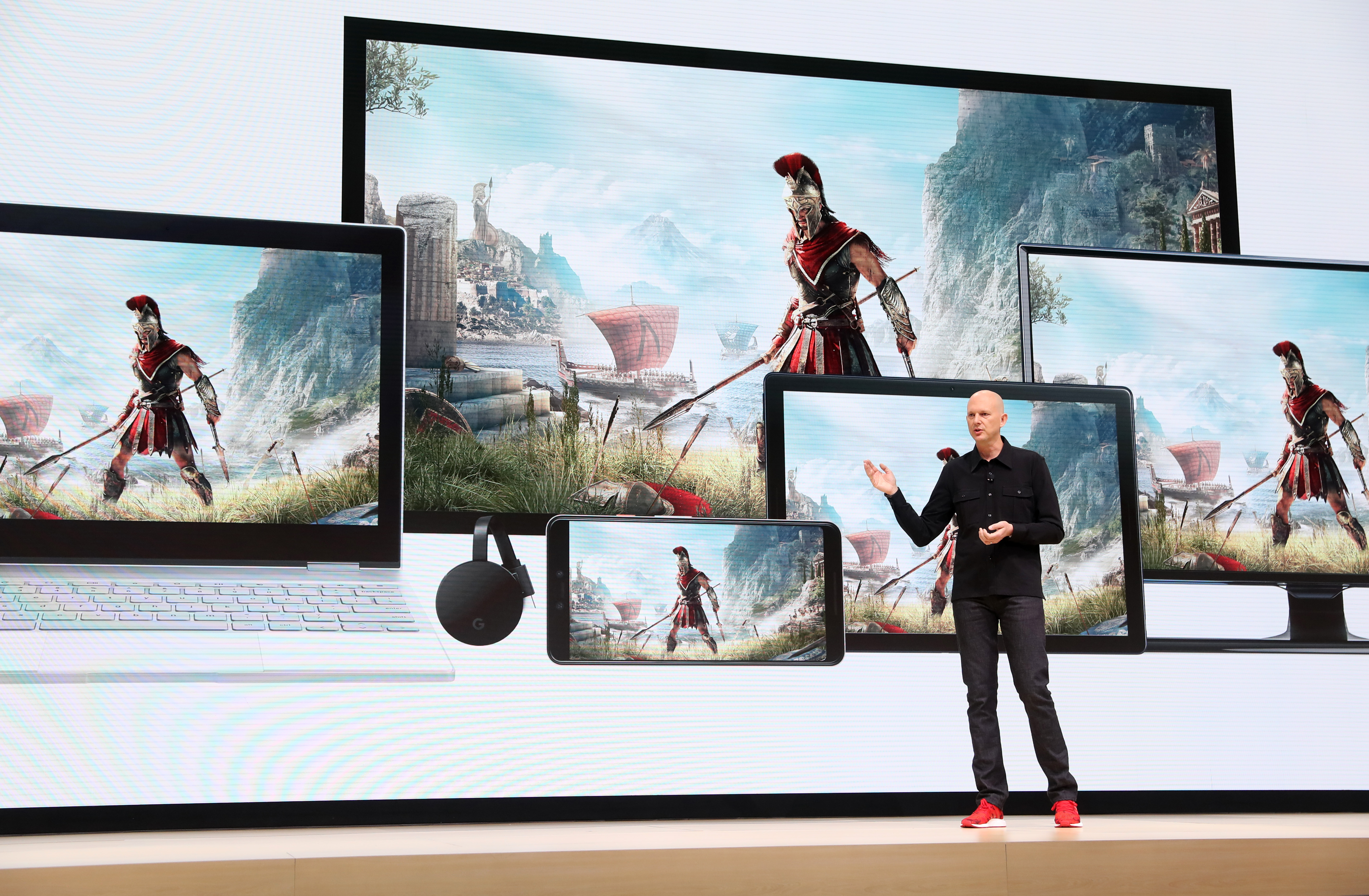 Phil Harrison presents Stadia, standing in front of a backdrop of devices playing Assassin's Creed Odyssey, at Google's GDC 2019 keynote.