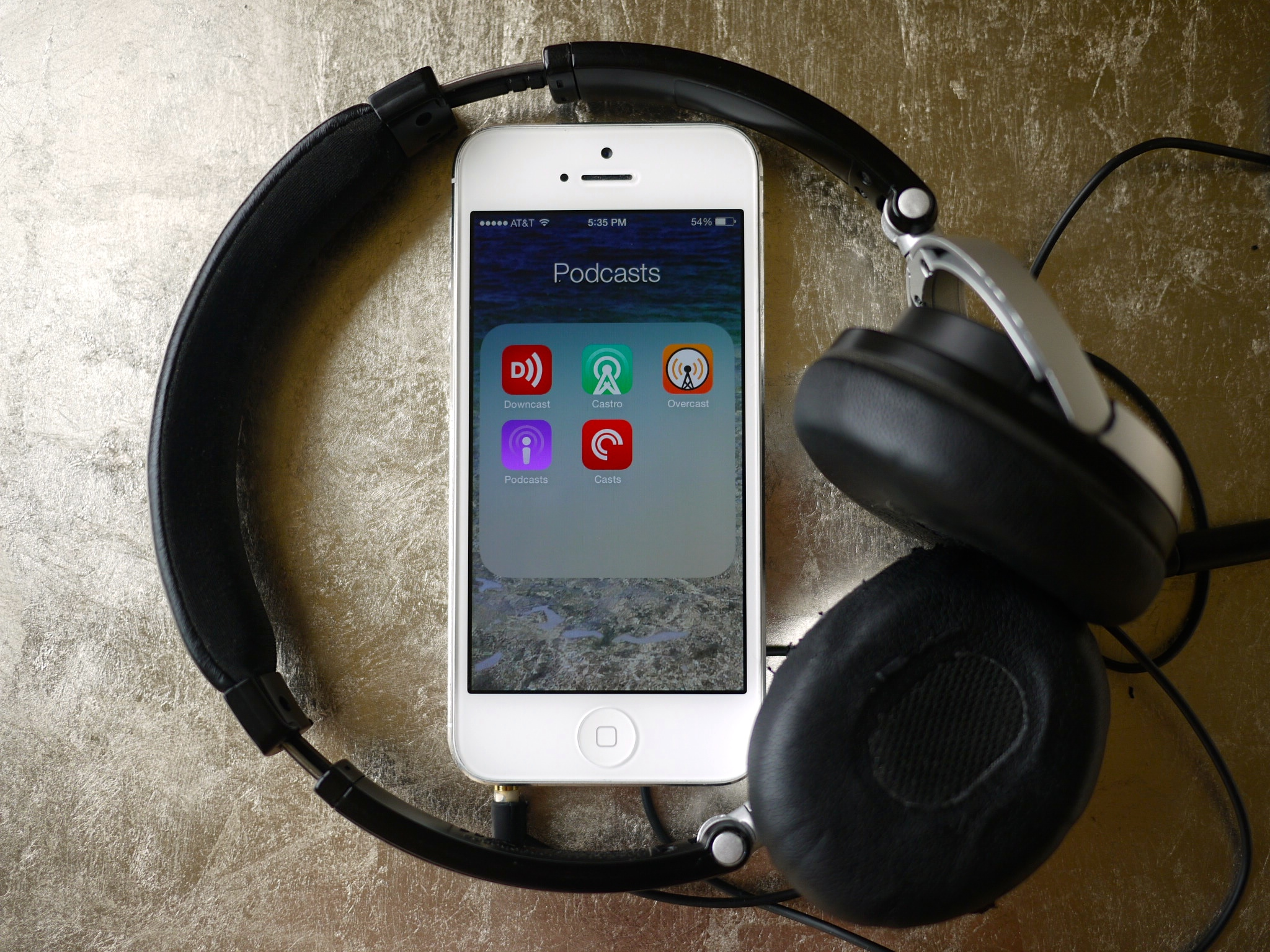 An iPhone with a pair of on-ear headphones surrounding it.
