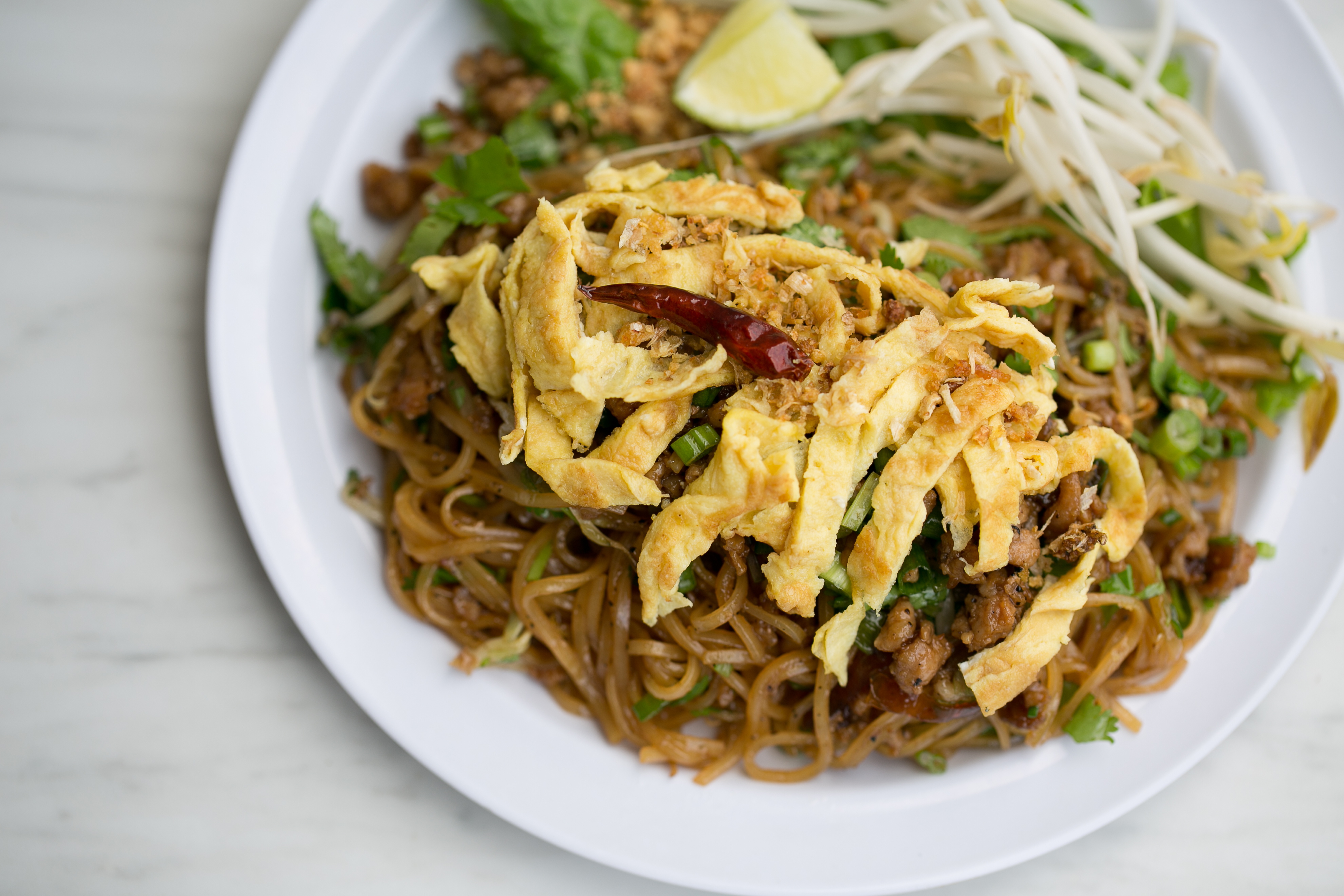 Kua mee, stir-fried rice noodles with ground pork, egg omelette, and crushed peanuts