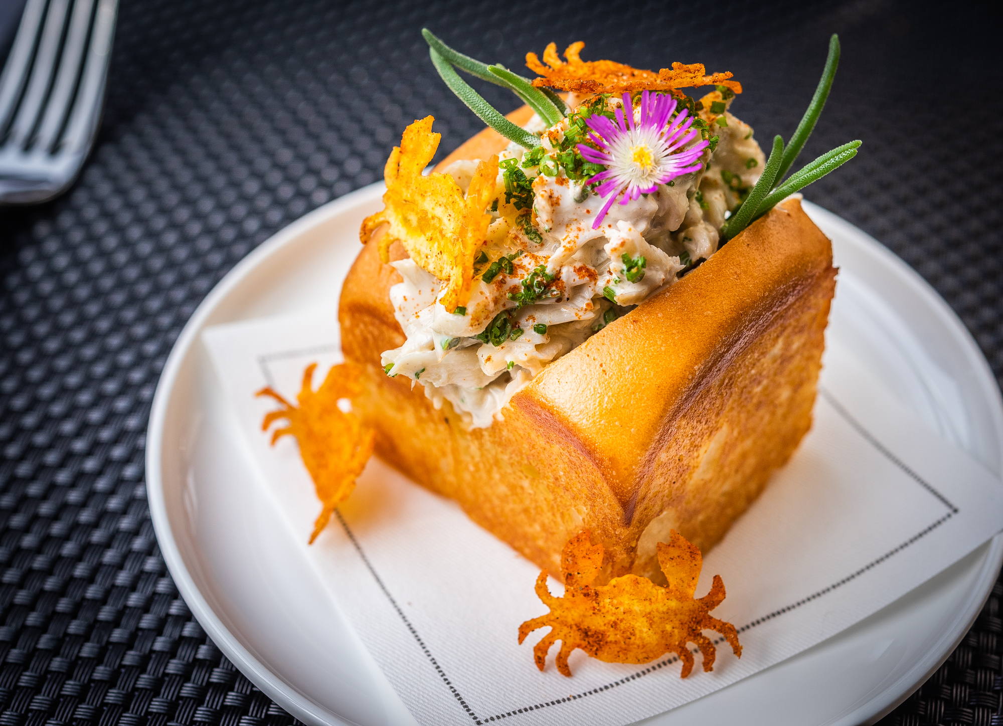 Estuary crab roll, with bread crab-shaped garnishes and edible flowers