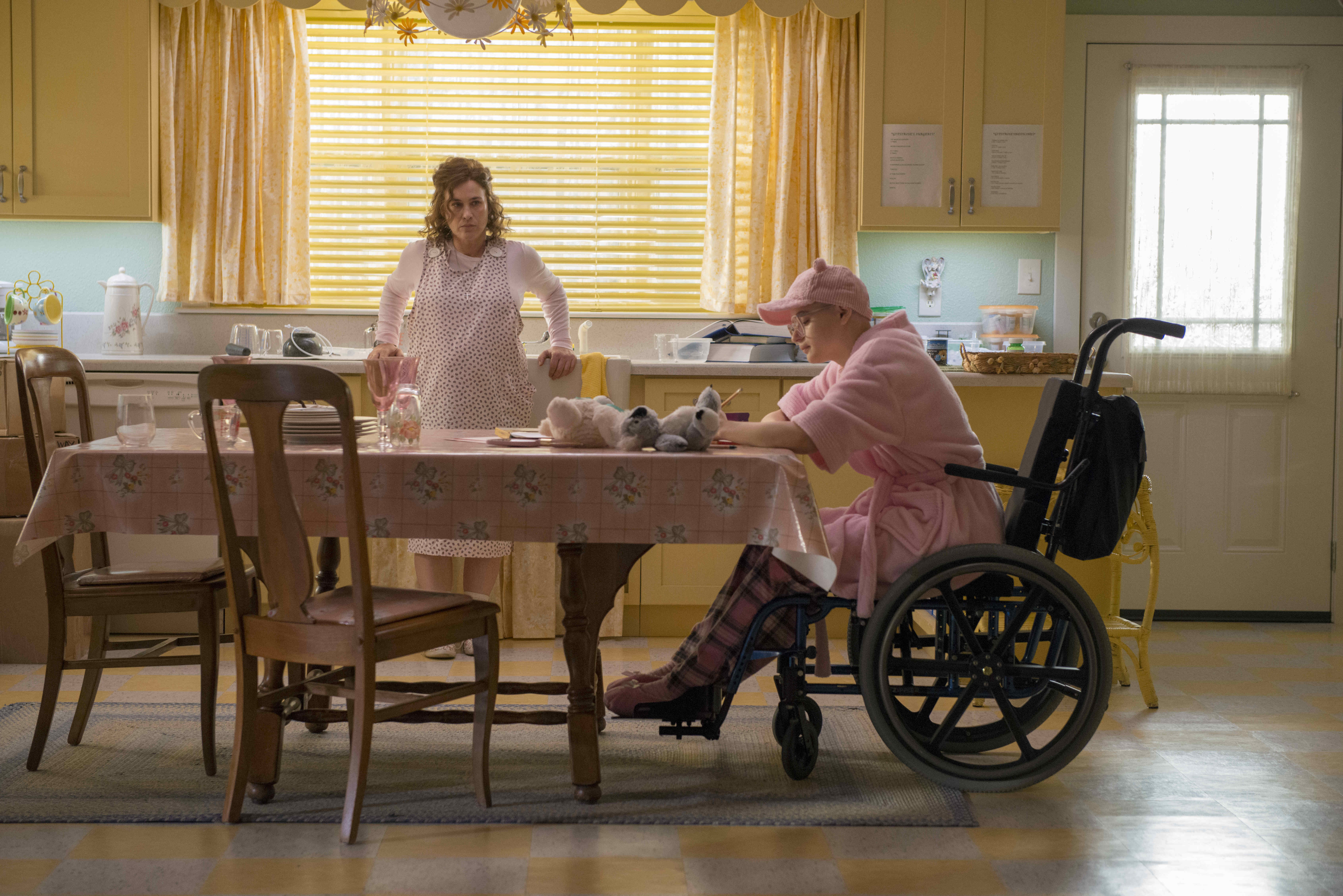 A woman stands at a kitchen table where another woman sits in a wheelchair.