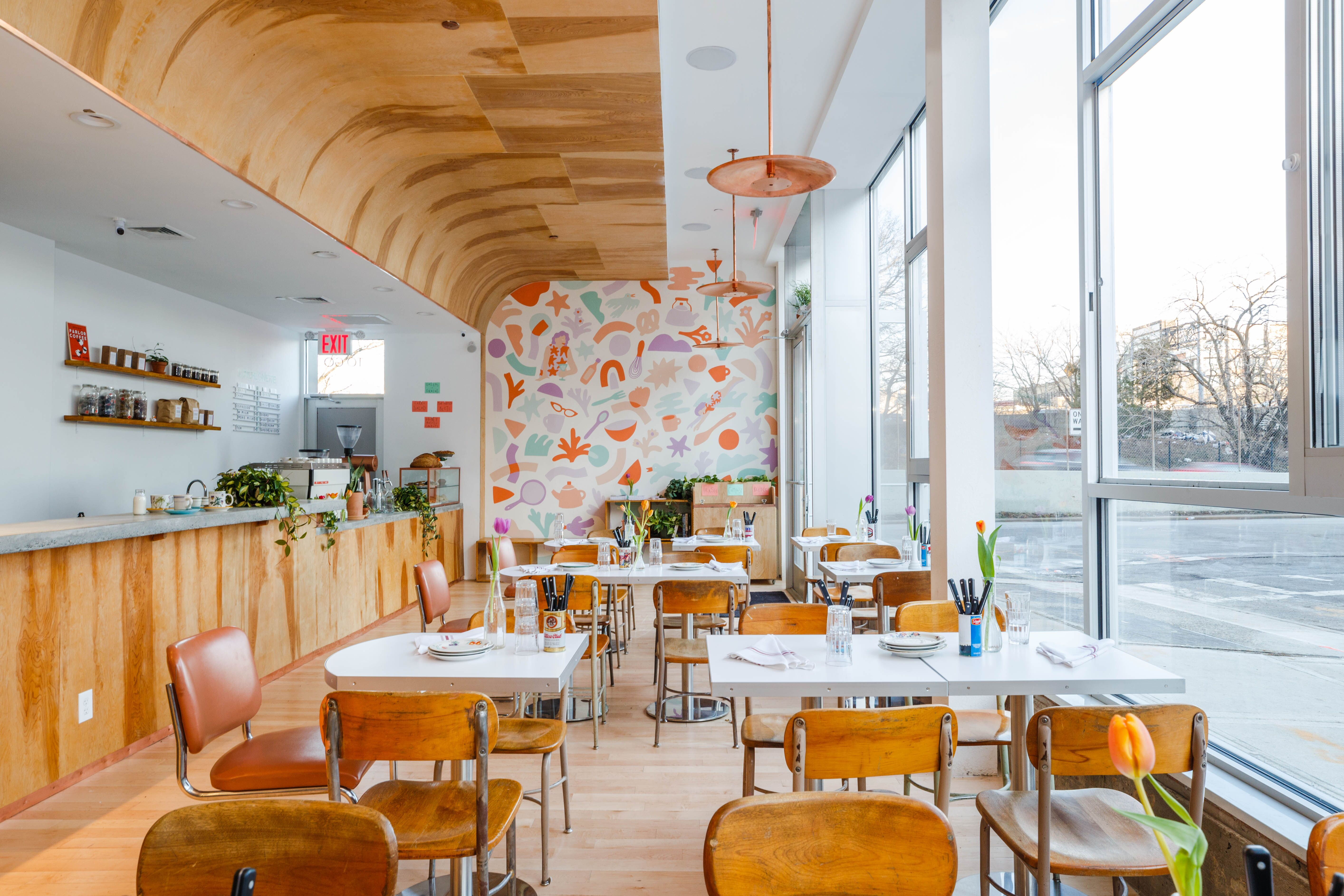 The interior at Gertie has windows on the left and a pastel-colored geometric mural on the back