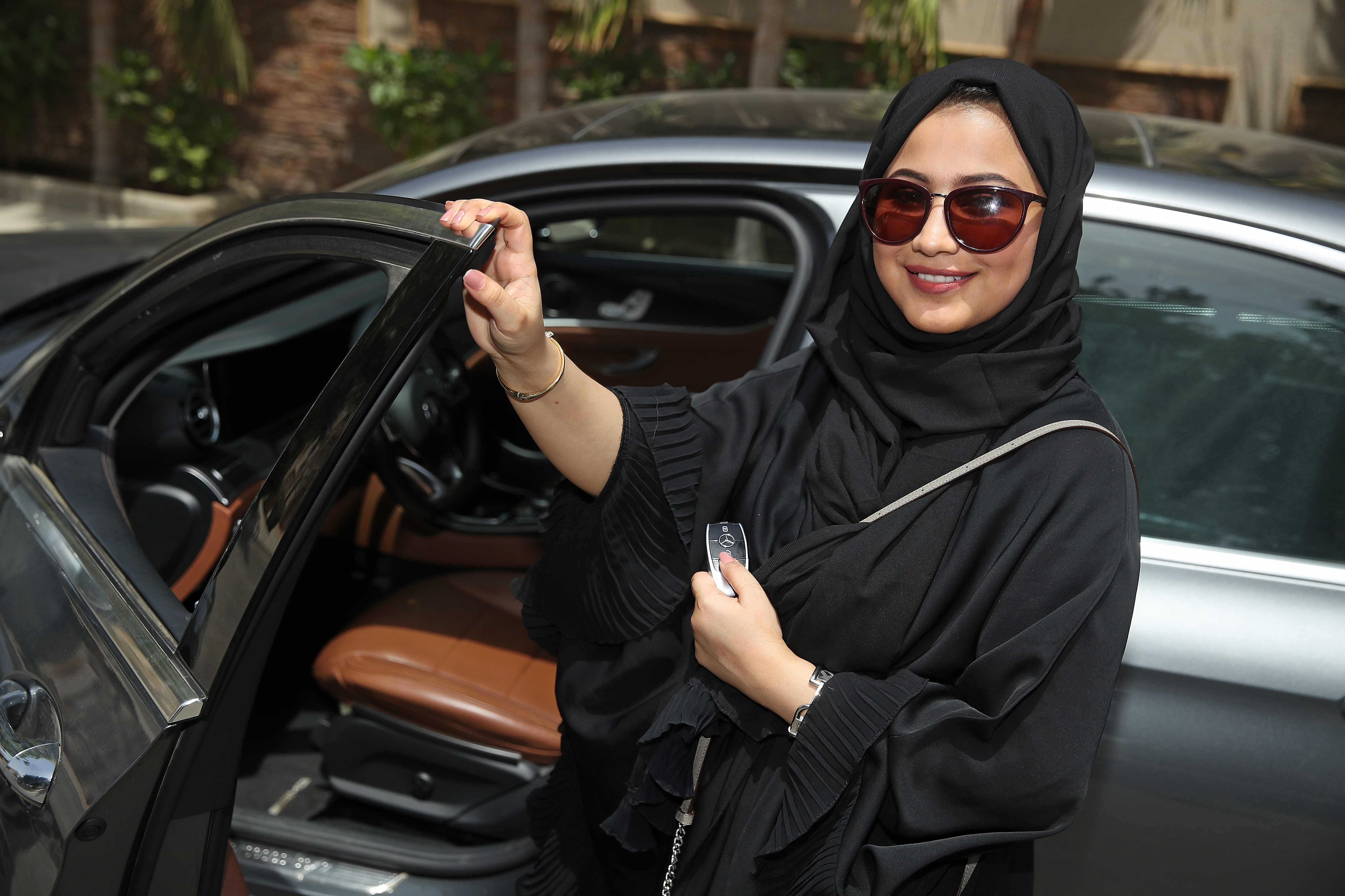 A woman wearing a headscarf stepping into the driver's seat on a car.