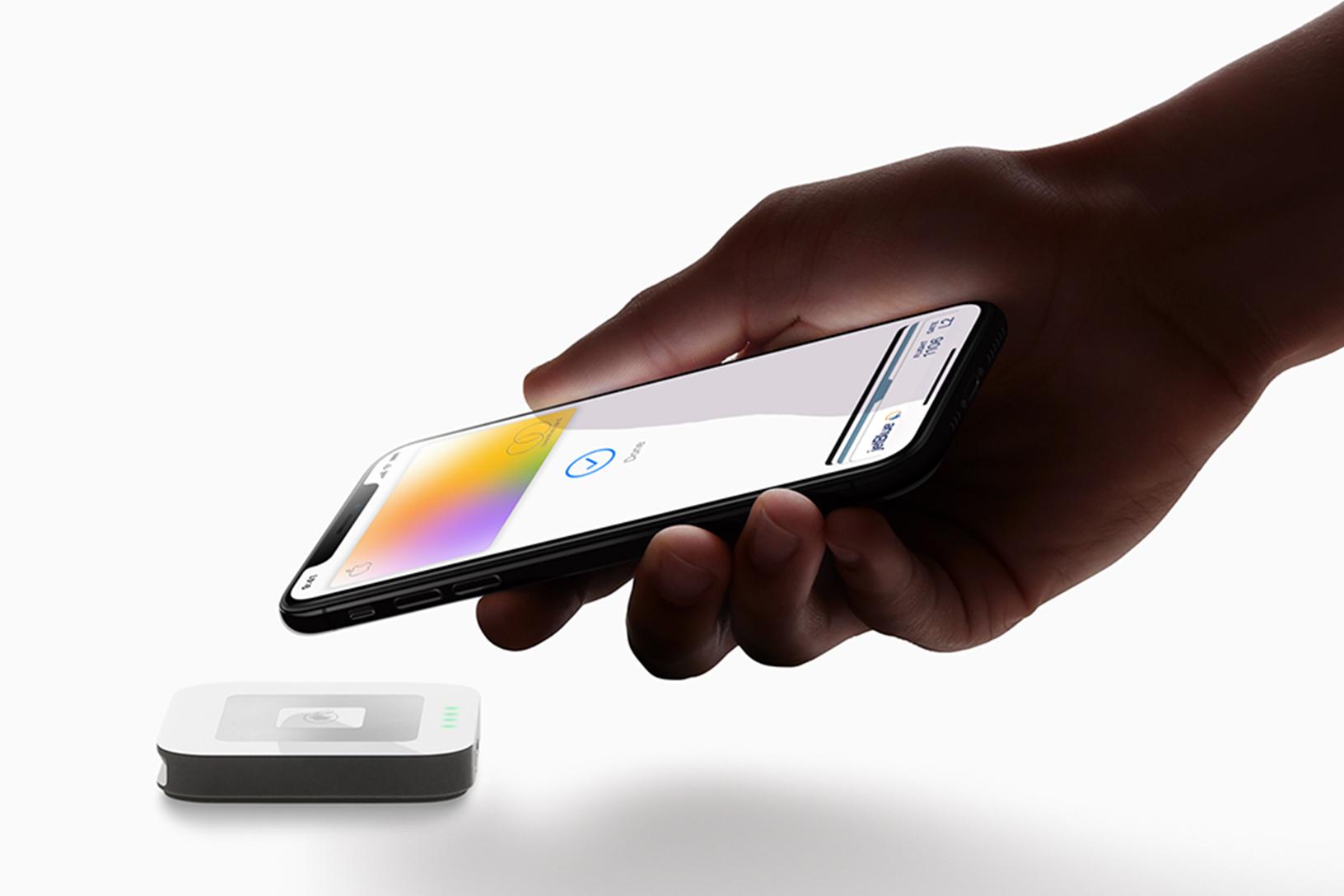 A hand extends an iPhone toward a contactless credit card reader.