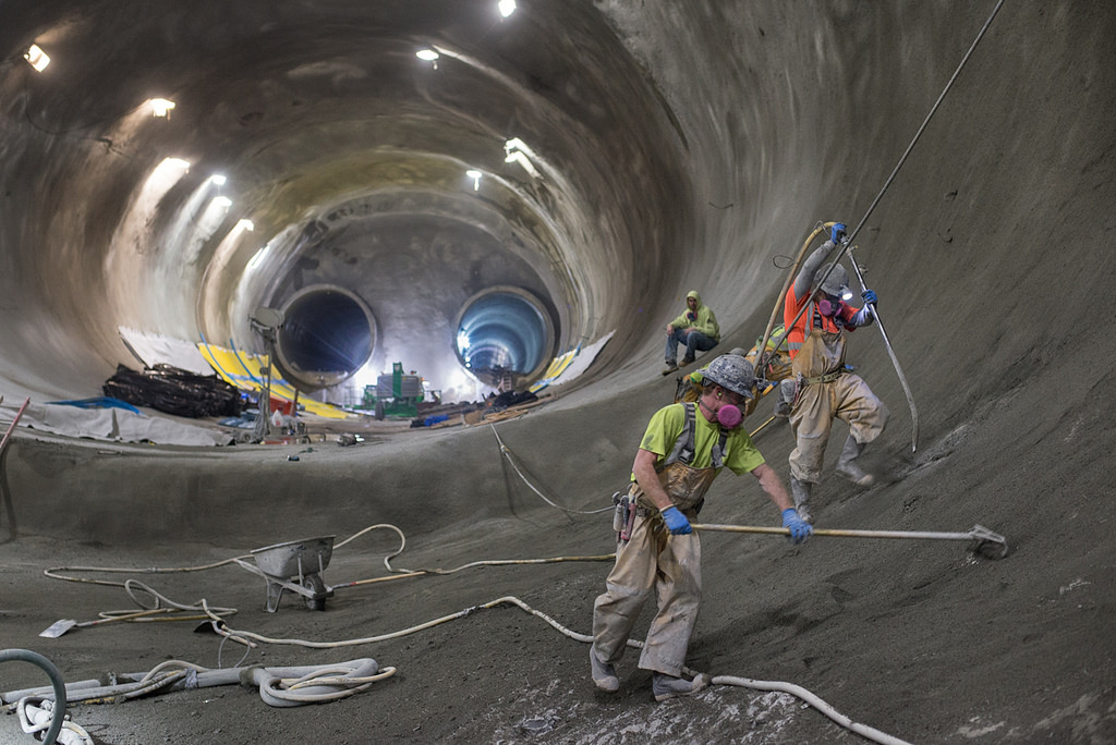 Workers cleaning up the interior of a huge underground subway tunnel.