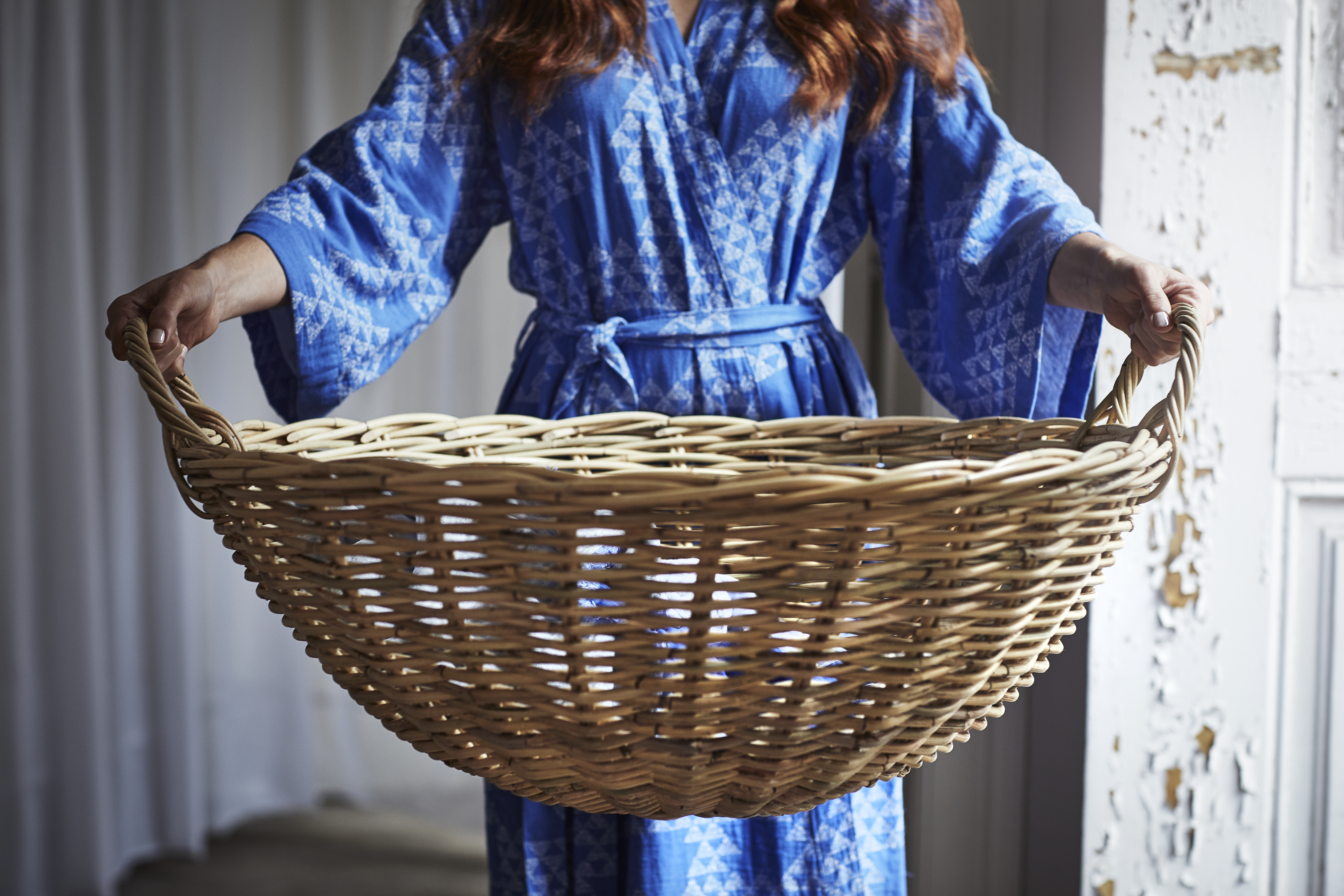 Woman in blue robe holding rattan basket